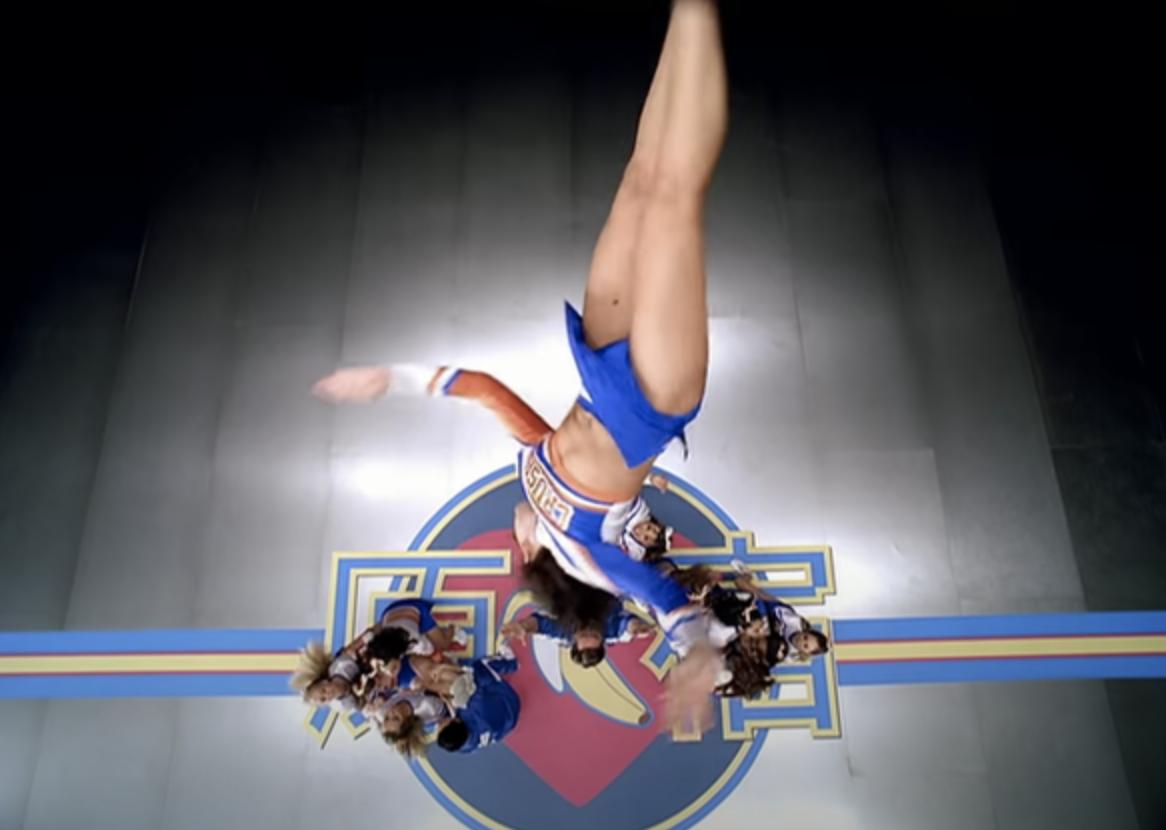 An aerial shot of a cheerleader doing a flip