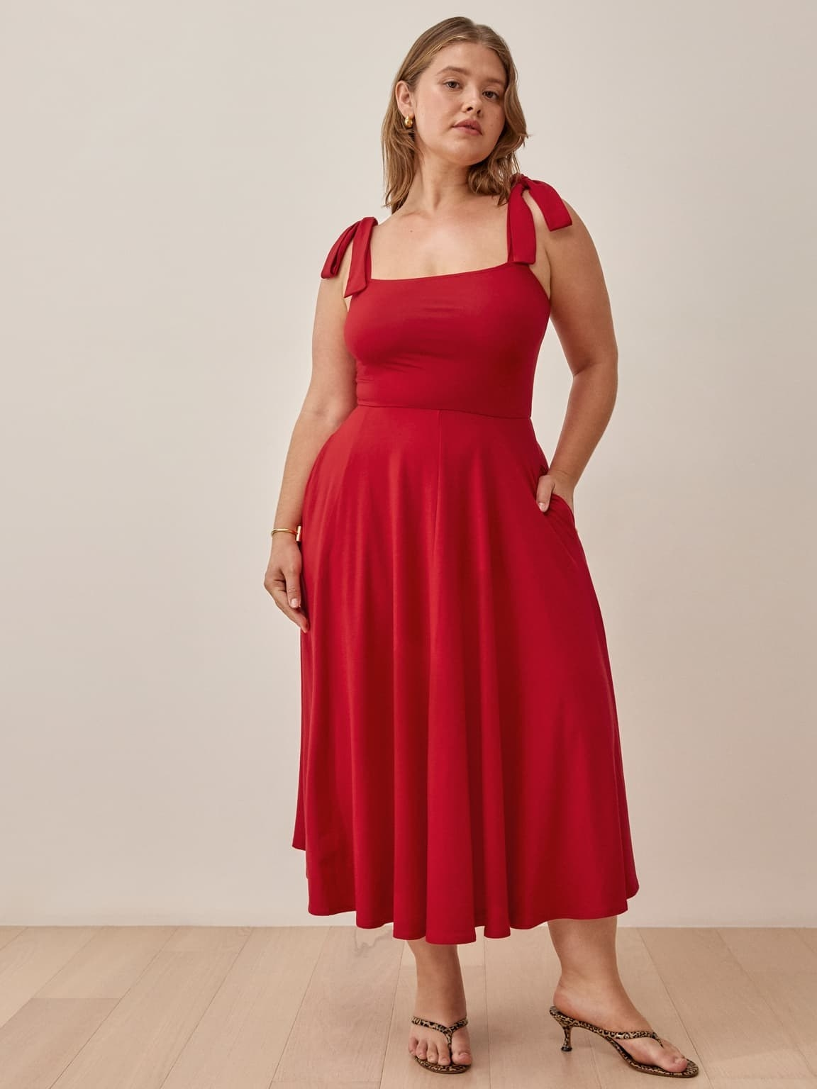 model wearing the calf-length tank dress in red with bows on top of either shoulder