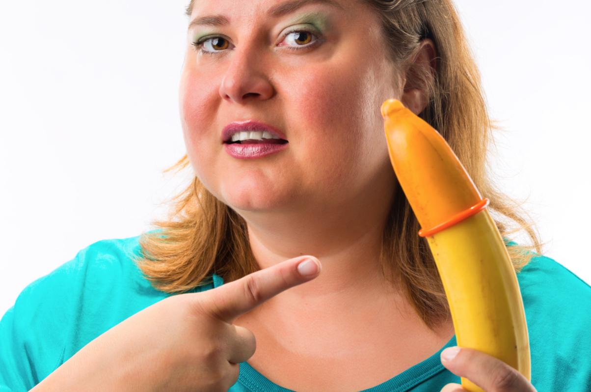 Woman pointing at condom on banana