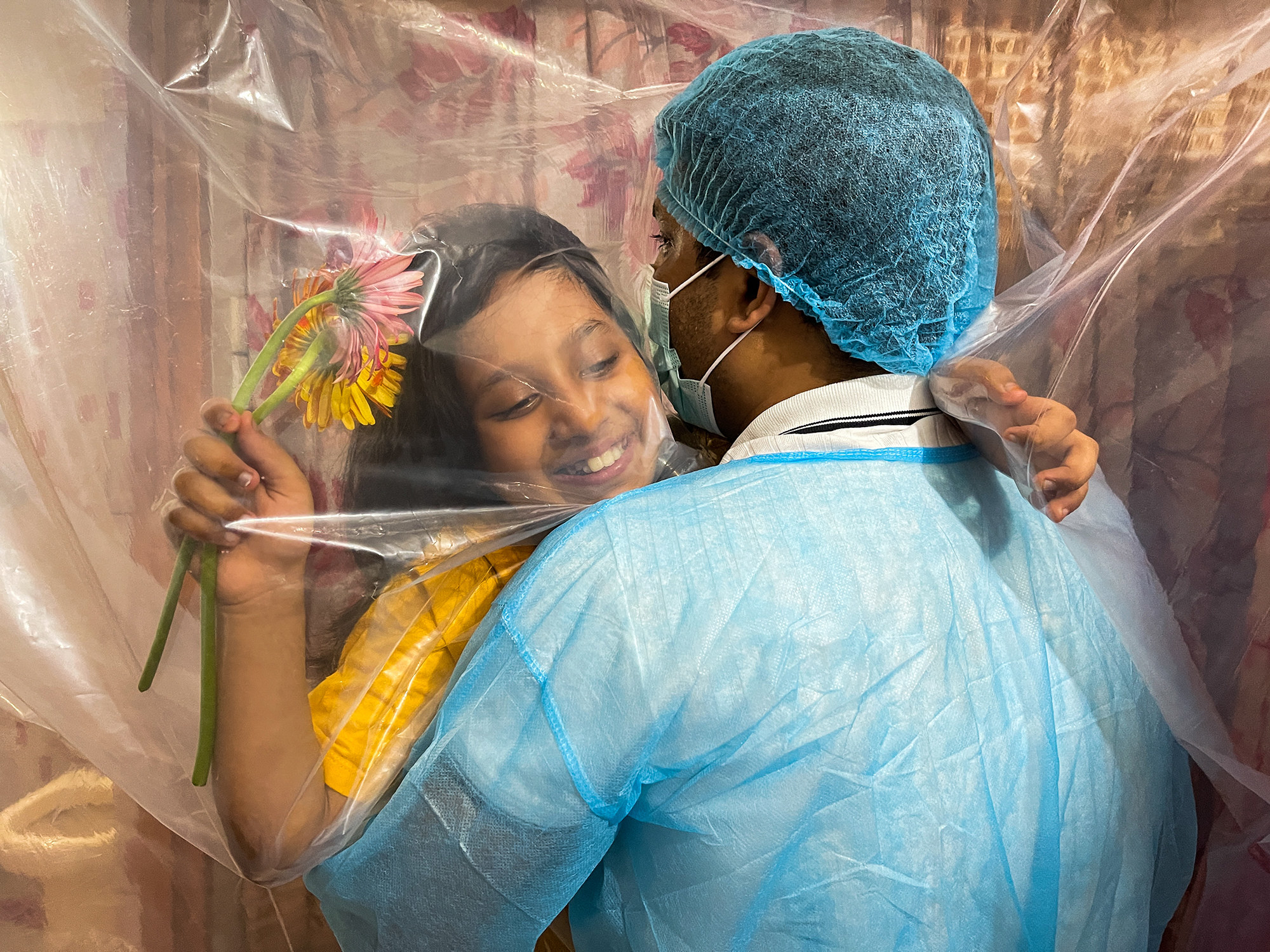 A smiling girl holding flowers hugs a doctor in scrubs through plastic