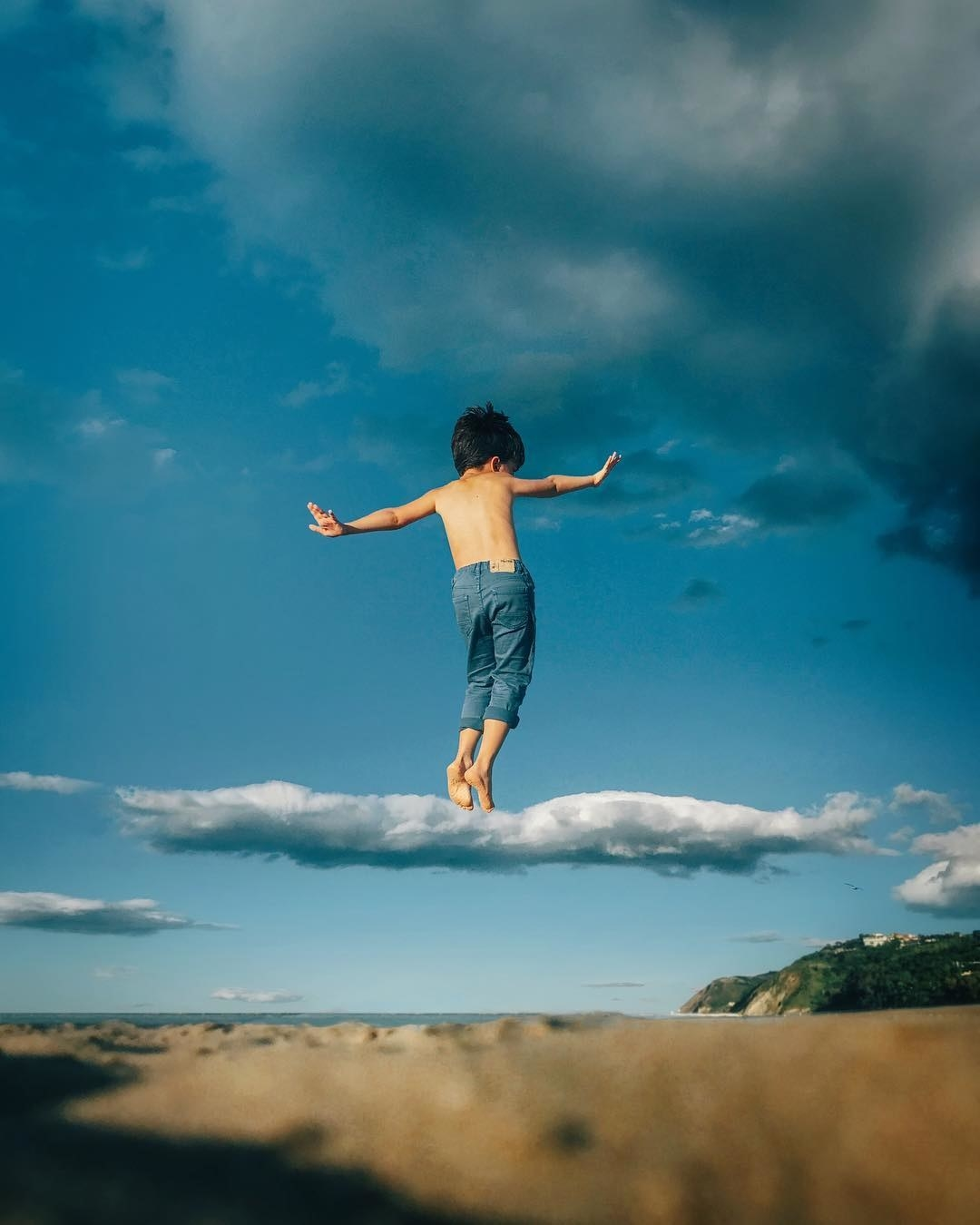 A young boy in mid-air seems to balance their tip-toes on a cloud