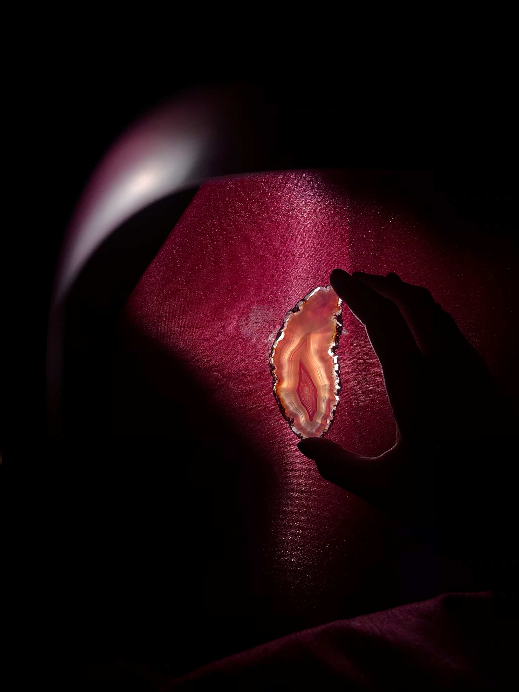 A slice of a crystal being held up to the light