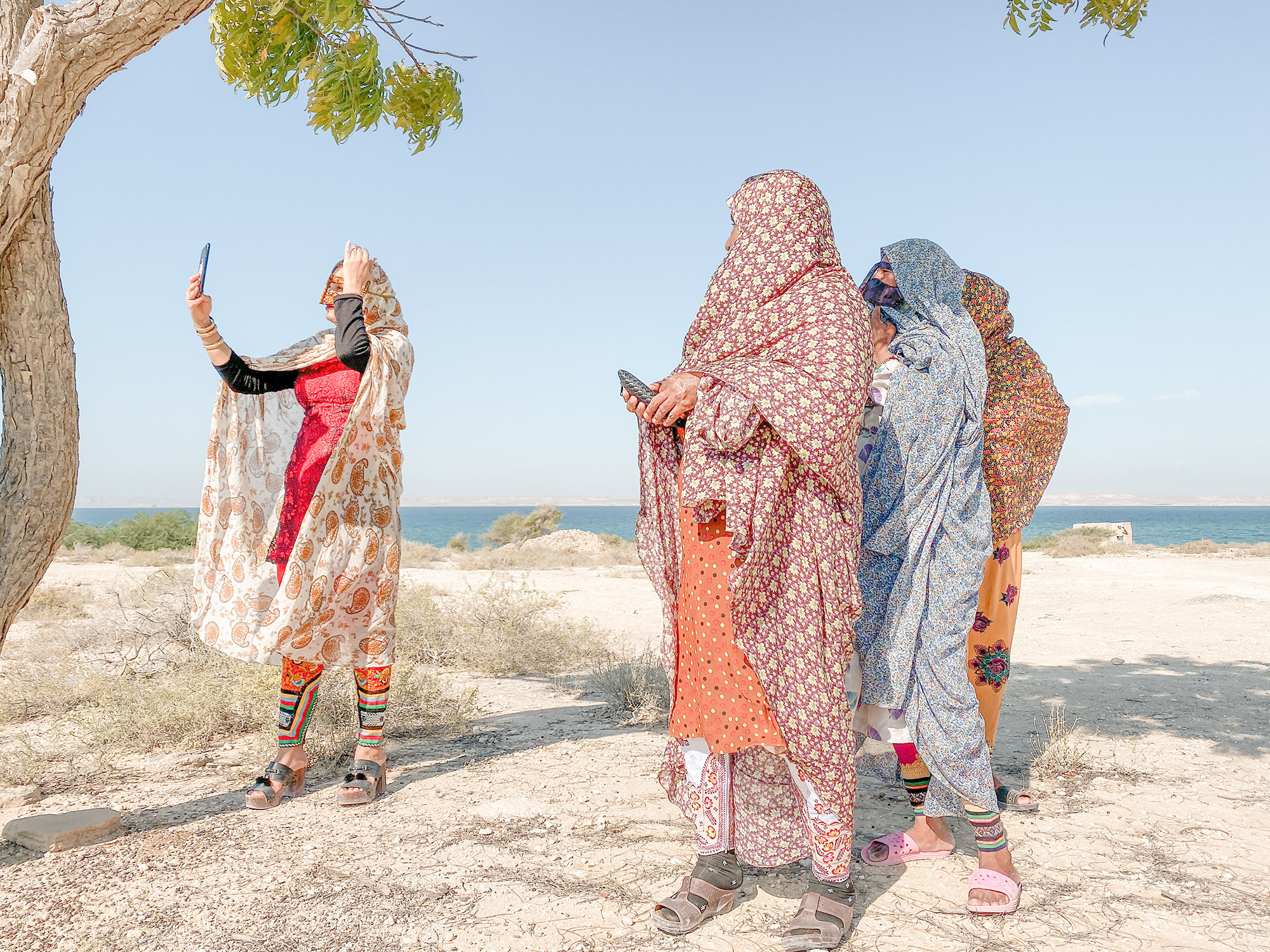 Four women in burkas standing on the seashore holding up their phones and taking selfies