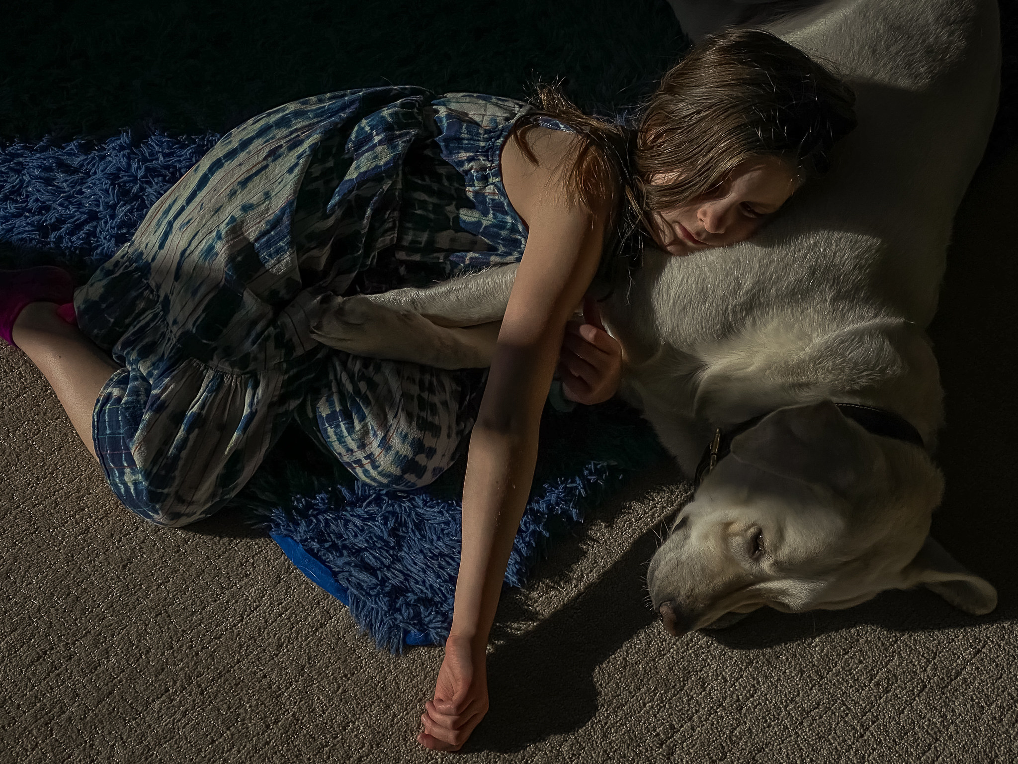 A girl sleeping on the floor with a dog at night