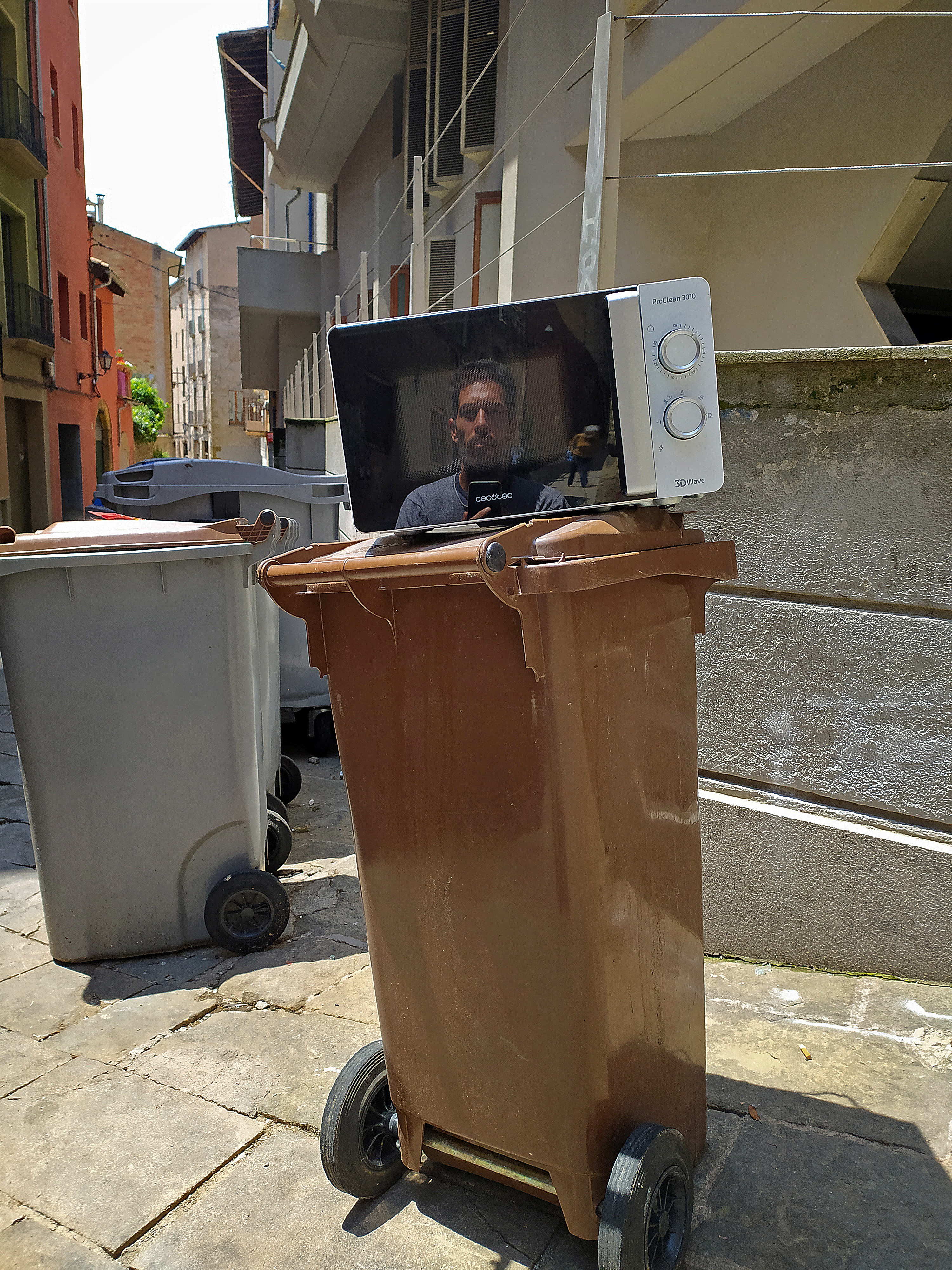 Someone is reflected in a microwave atop a garbage can on the street