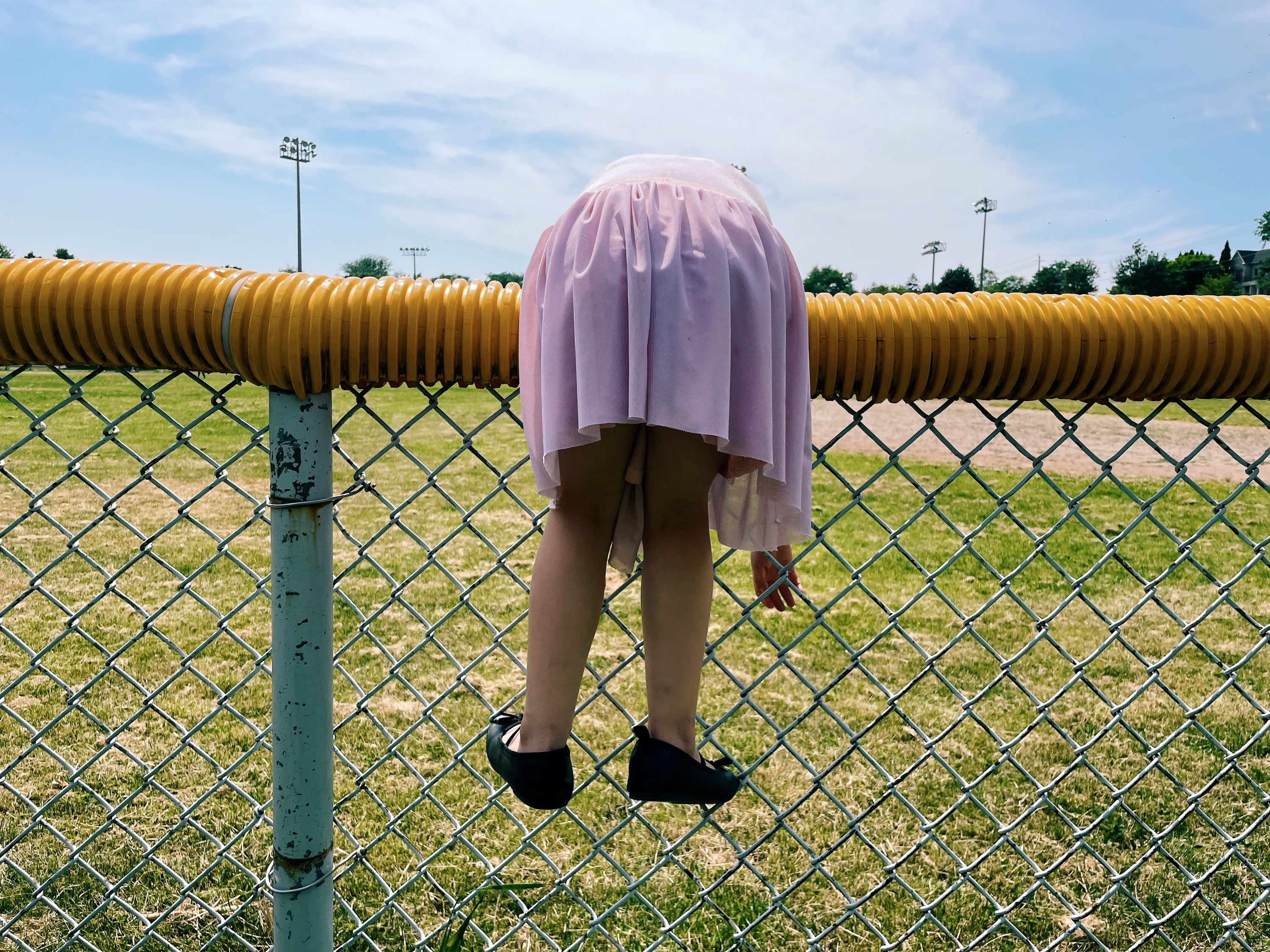 A girl in a dress hangs over a fence