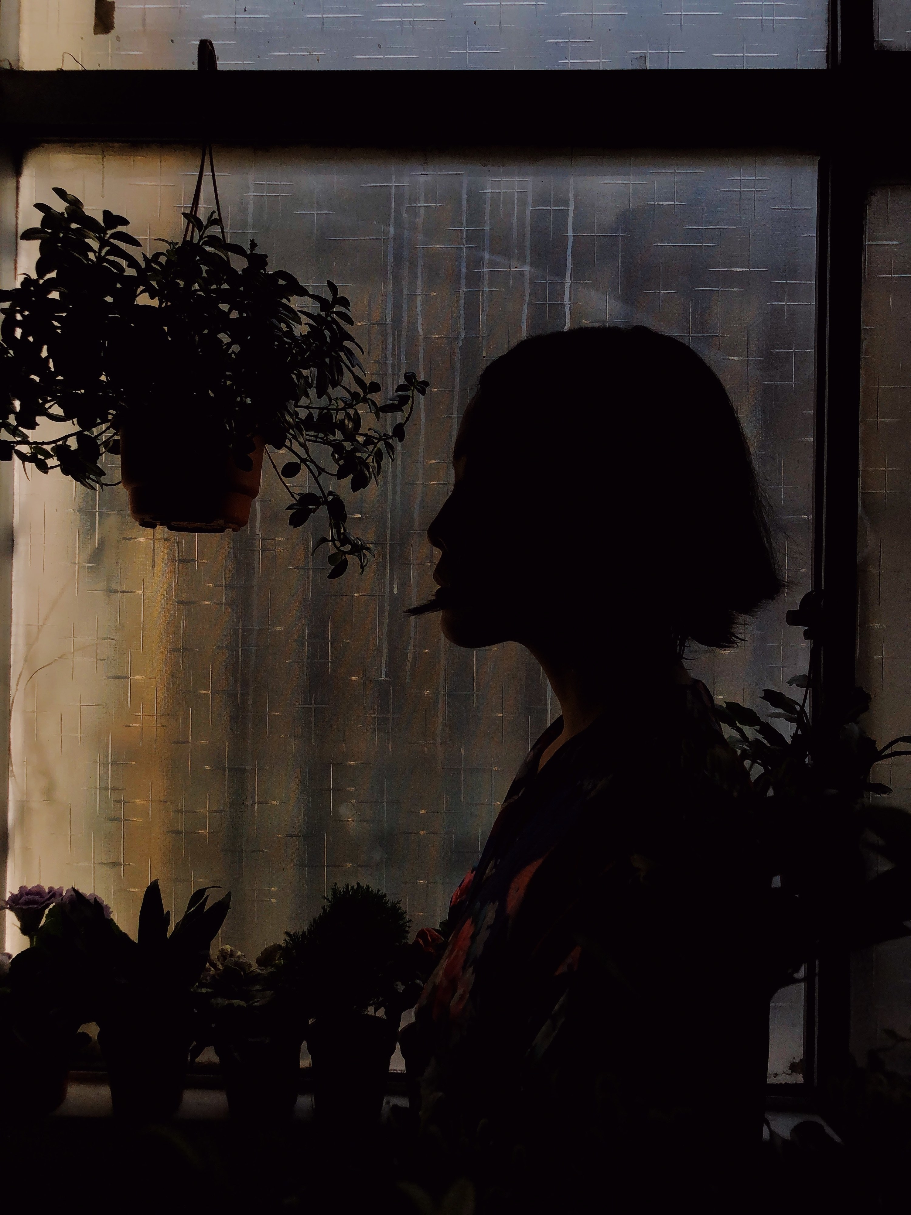 A woman in silhouette in front of a window in the dark