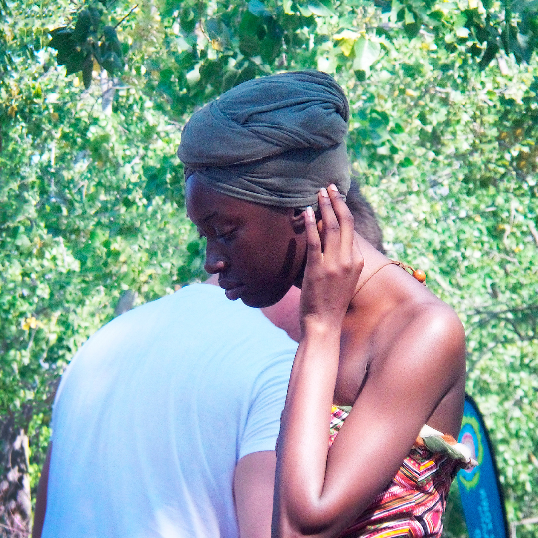 A woman wearing a head wrap and holding a hand to her face crosses paths with a man outside