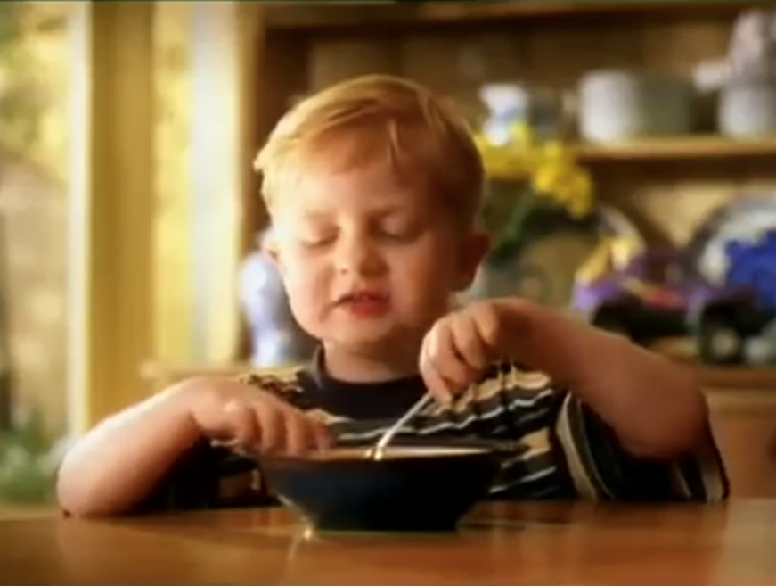 A young boy sits on a table and eats from a bowl filled with SPC fruit