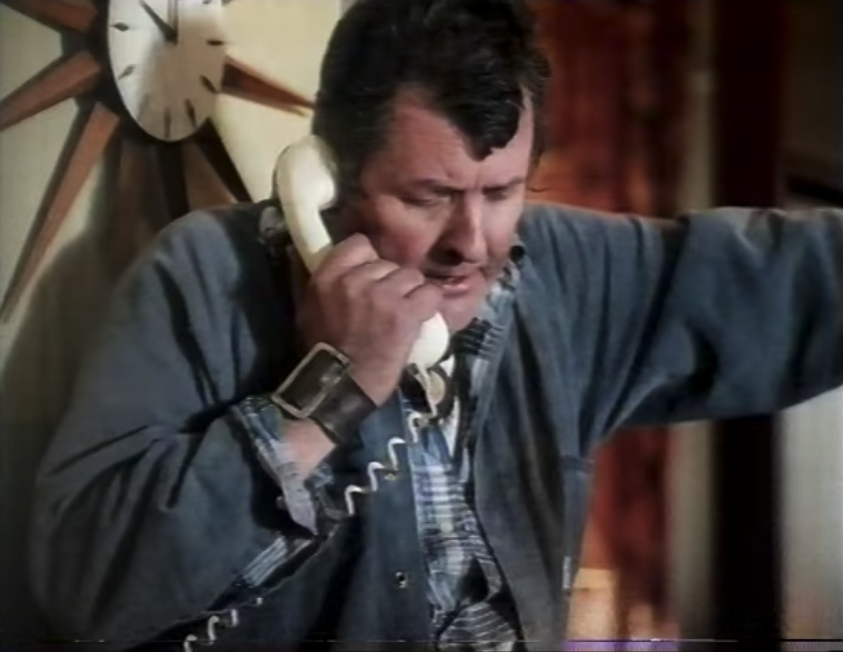 A man talking on the phone; it is a landline phone and he is holding it to his ear