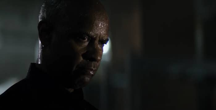 Denzel glaring, his face wet