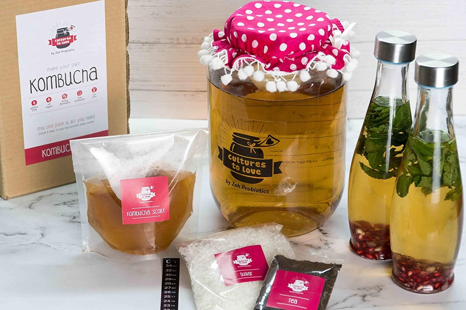 The kombucha brewing kit with the box, the SCOBY in a packet, jar and two bottles with Kombucha in them