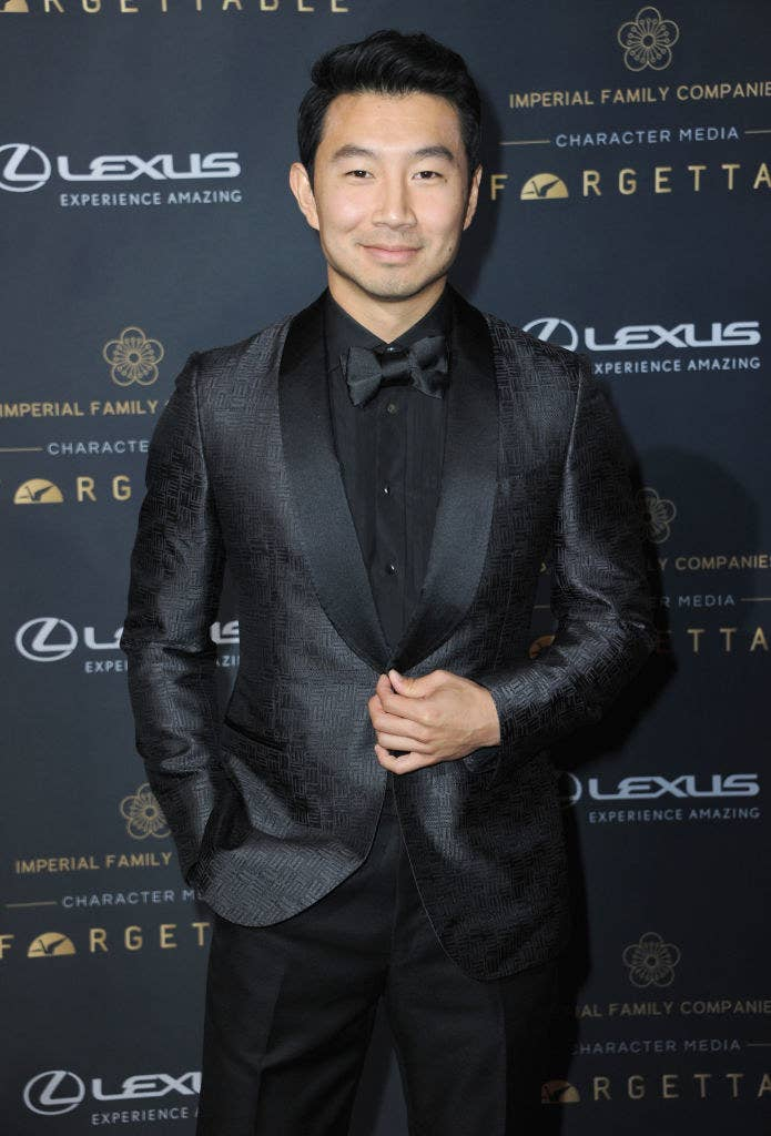 Simu Liu posing on a red carpet in a textured suit