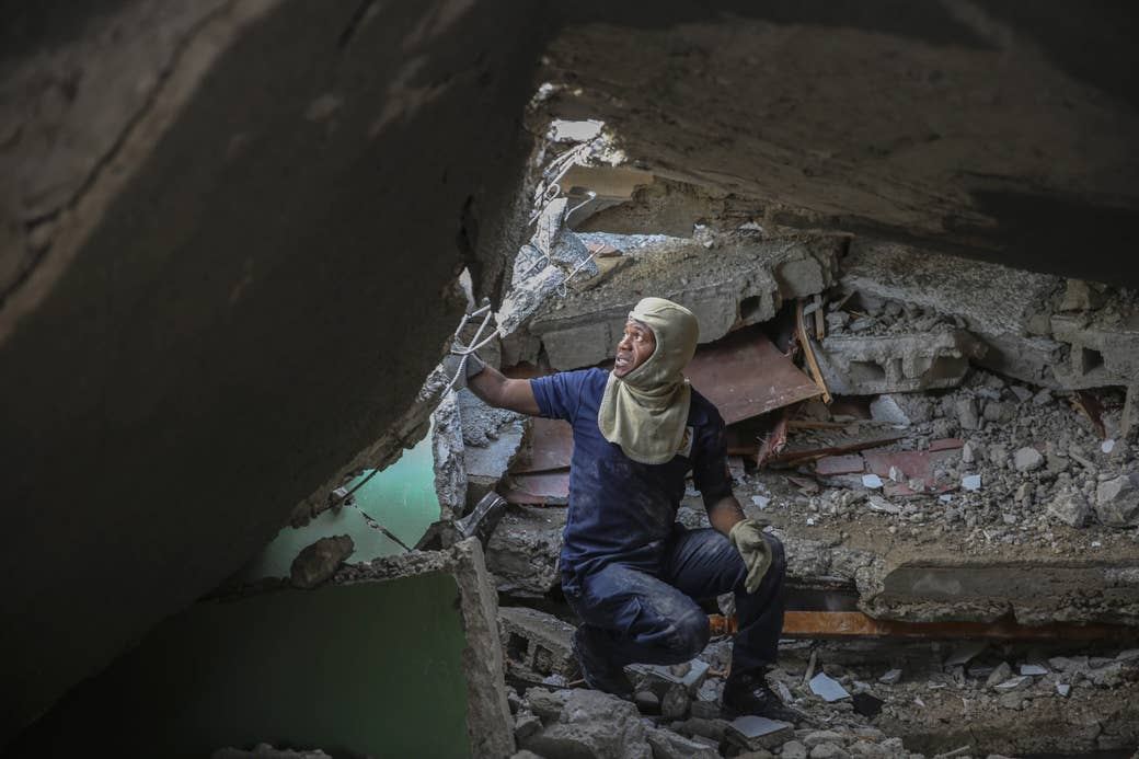 A man with protective headwear crouches and gazes upward amid rubble
