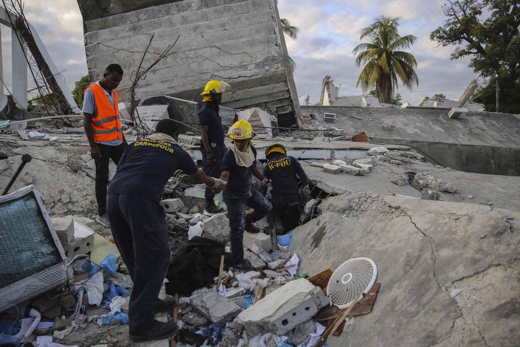 Five people, some in headgear, walk amid the rubble