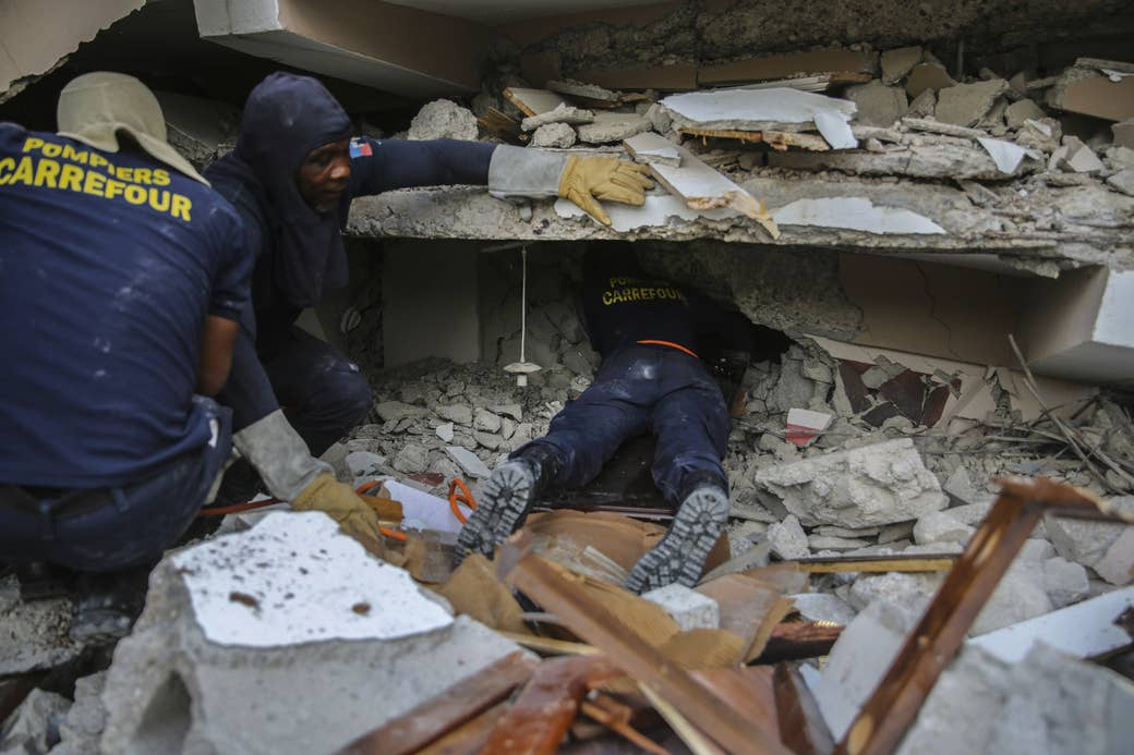 Three people crouch or lie flat amid rubble