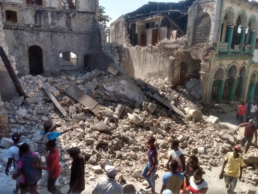 People walk alongside a huge mountain of rubble
