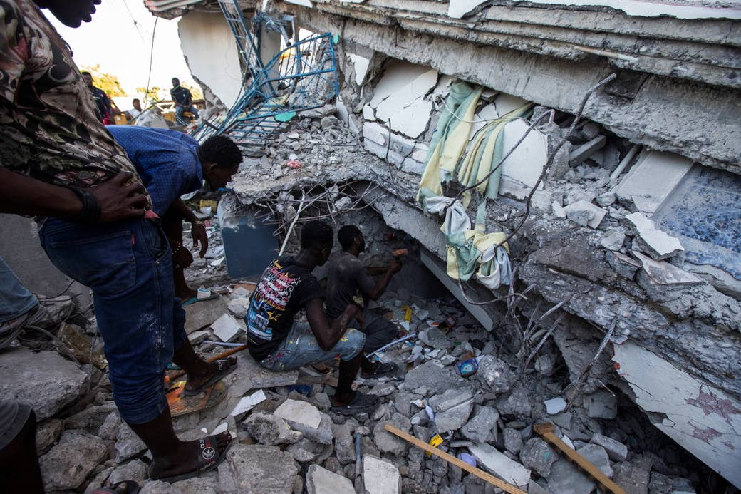People crouch and sit near extensive rubble