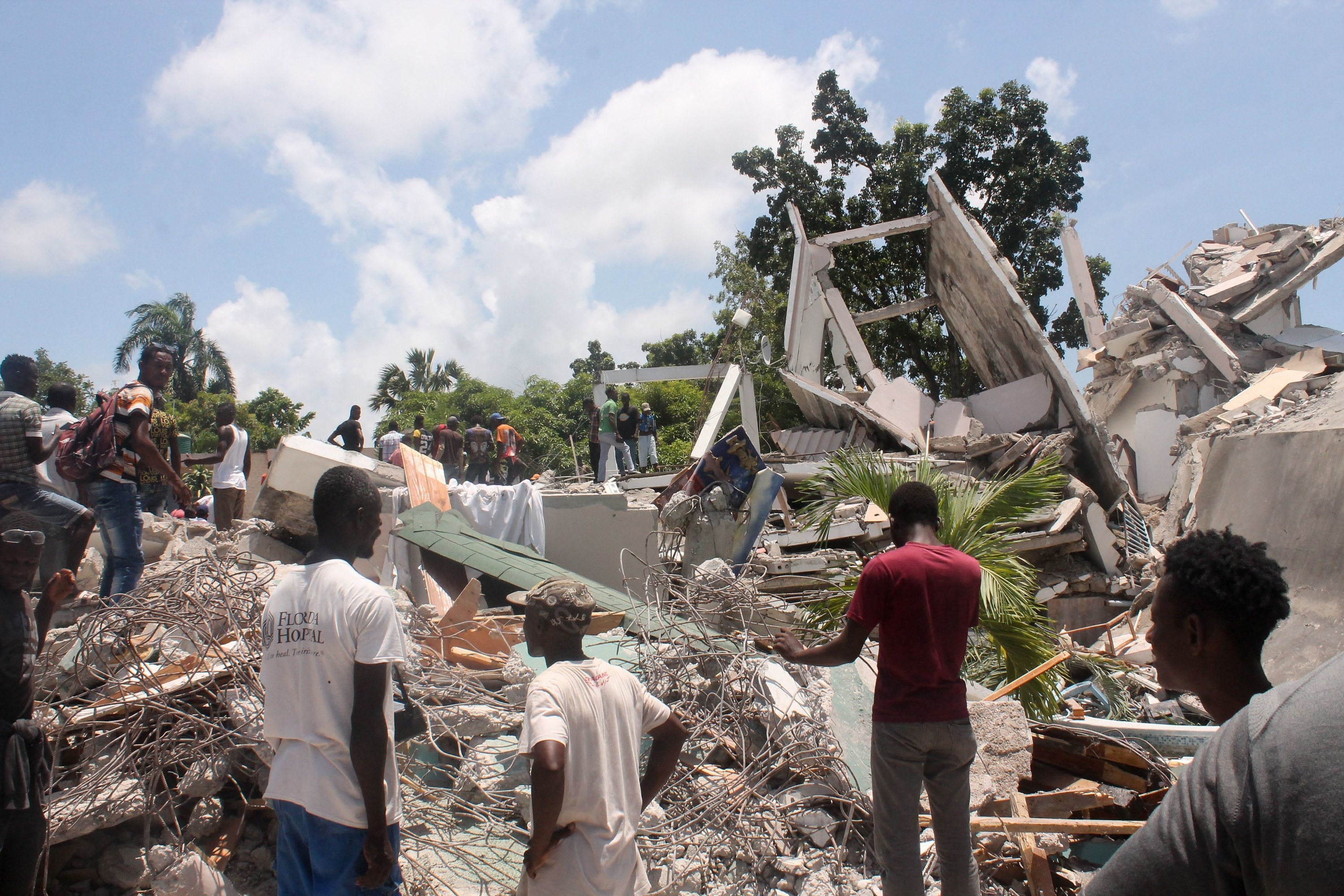 People walk on top of rubble and debris on a sunny day