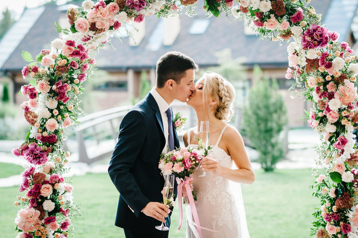 Groom and bride kissing at their wedding underneath a flower arch