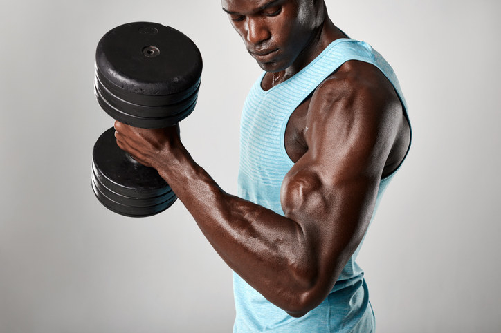 Man with big muscles lifting weights