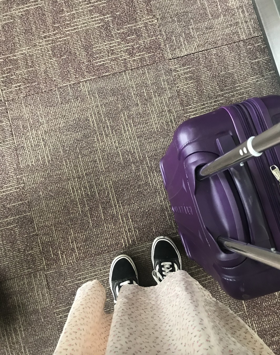 Image of a person's feet with a rolly carry-on suitcase