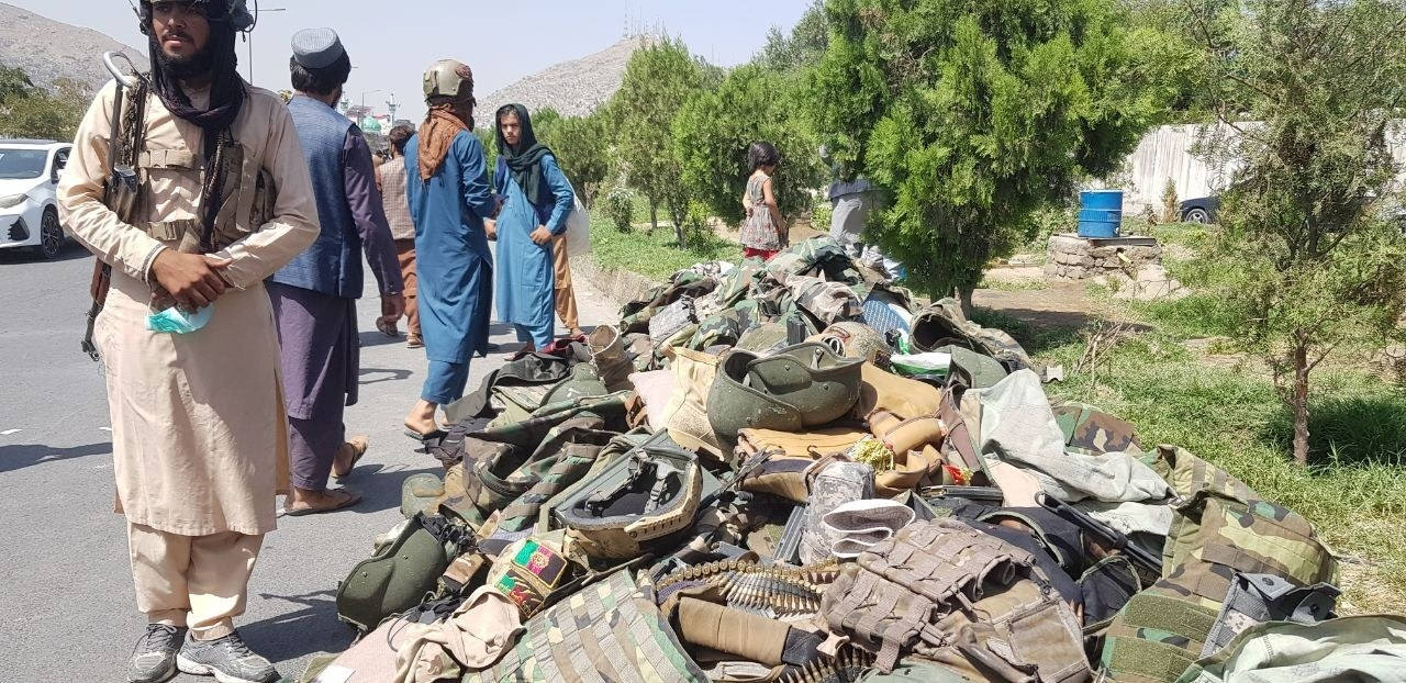 Military equipment, helmets, flak jackets and ammunition is seen piled alongside the road next to Taliban fighters.
