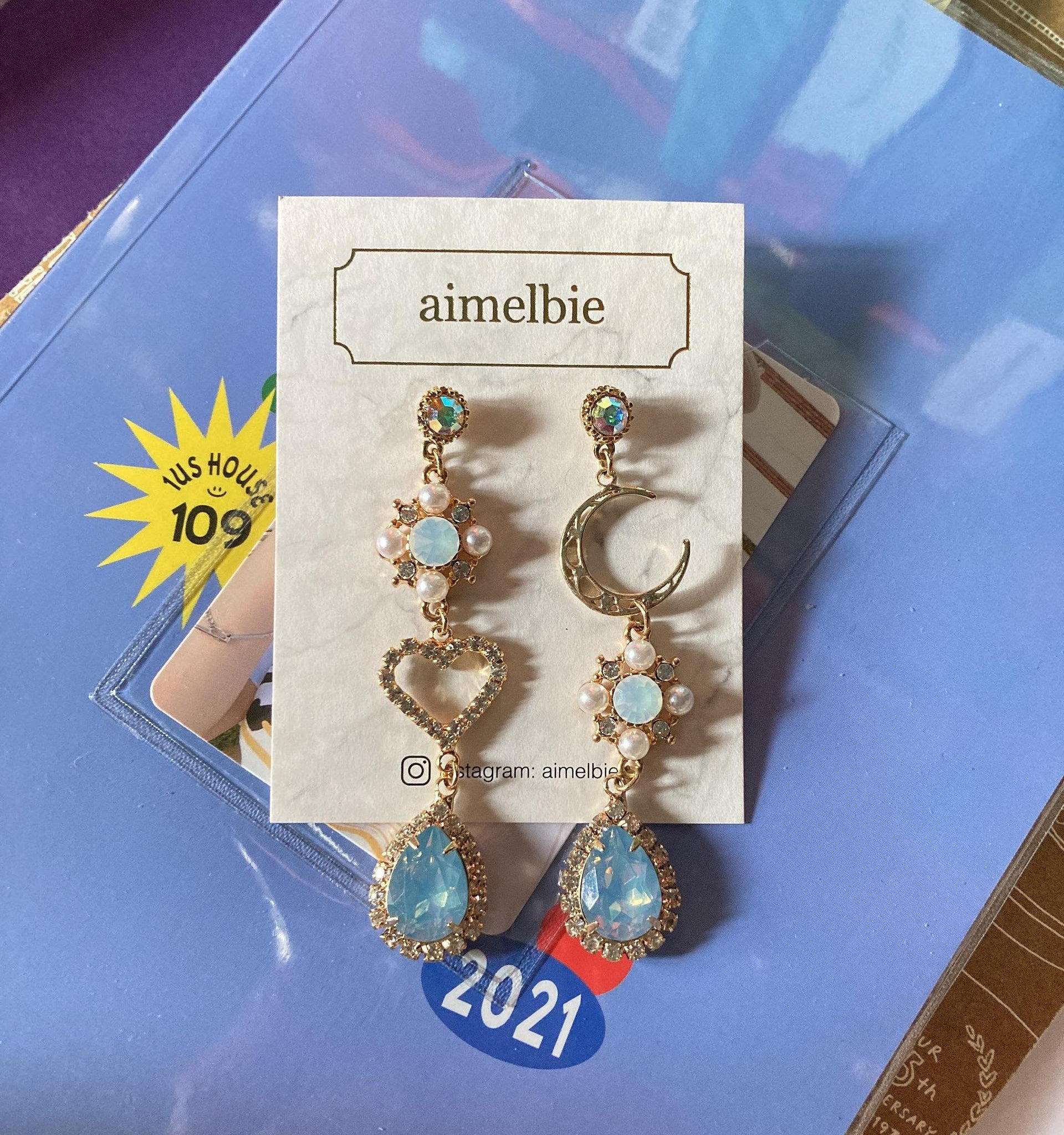 coordinating gold dangly earrings with light blue stones, one with a heart and one with a moon