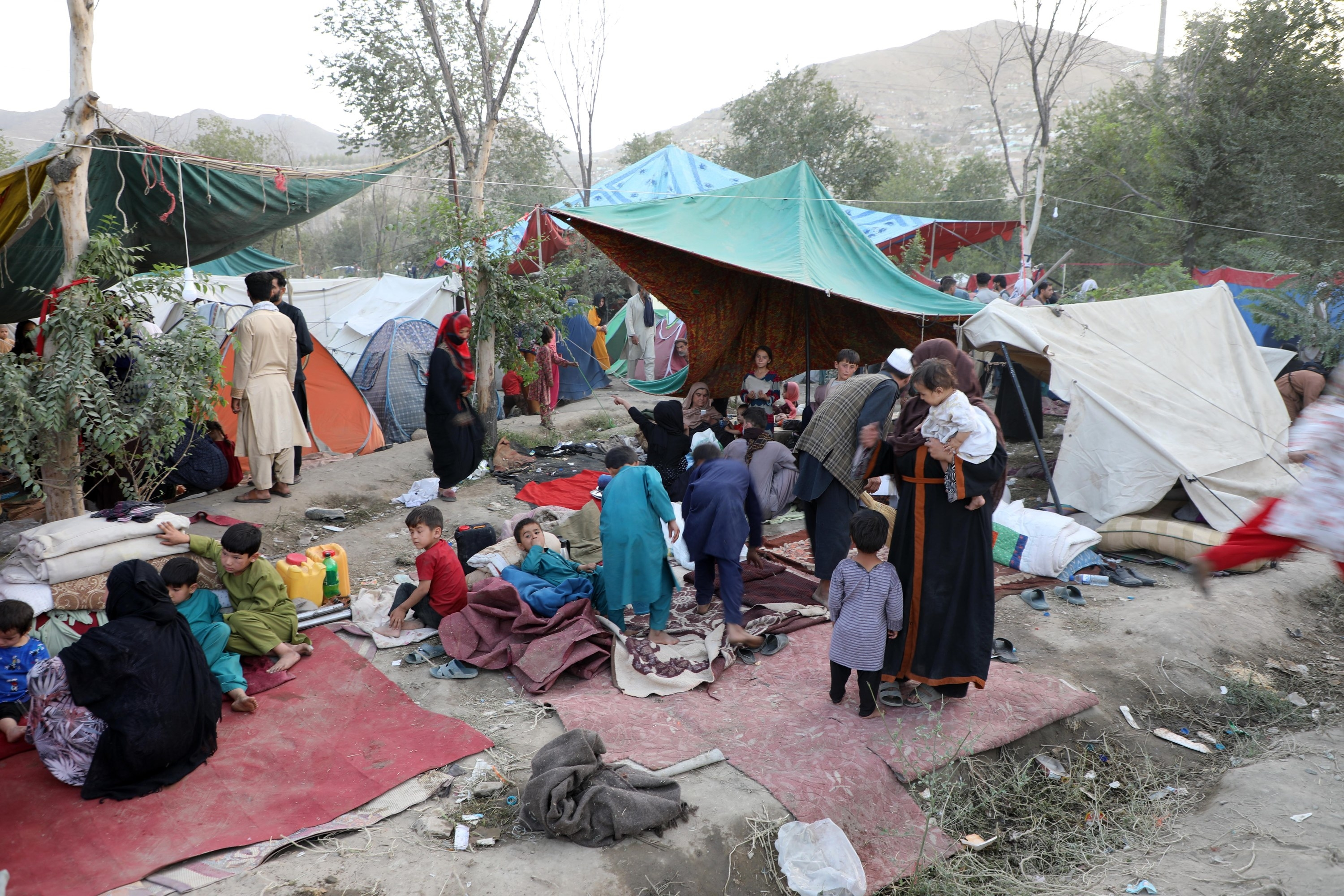 Makeshift tents and children sleeping on the ground near their families
