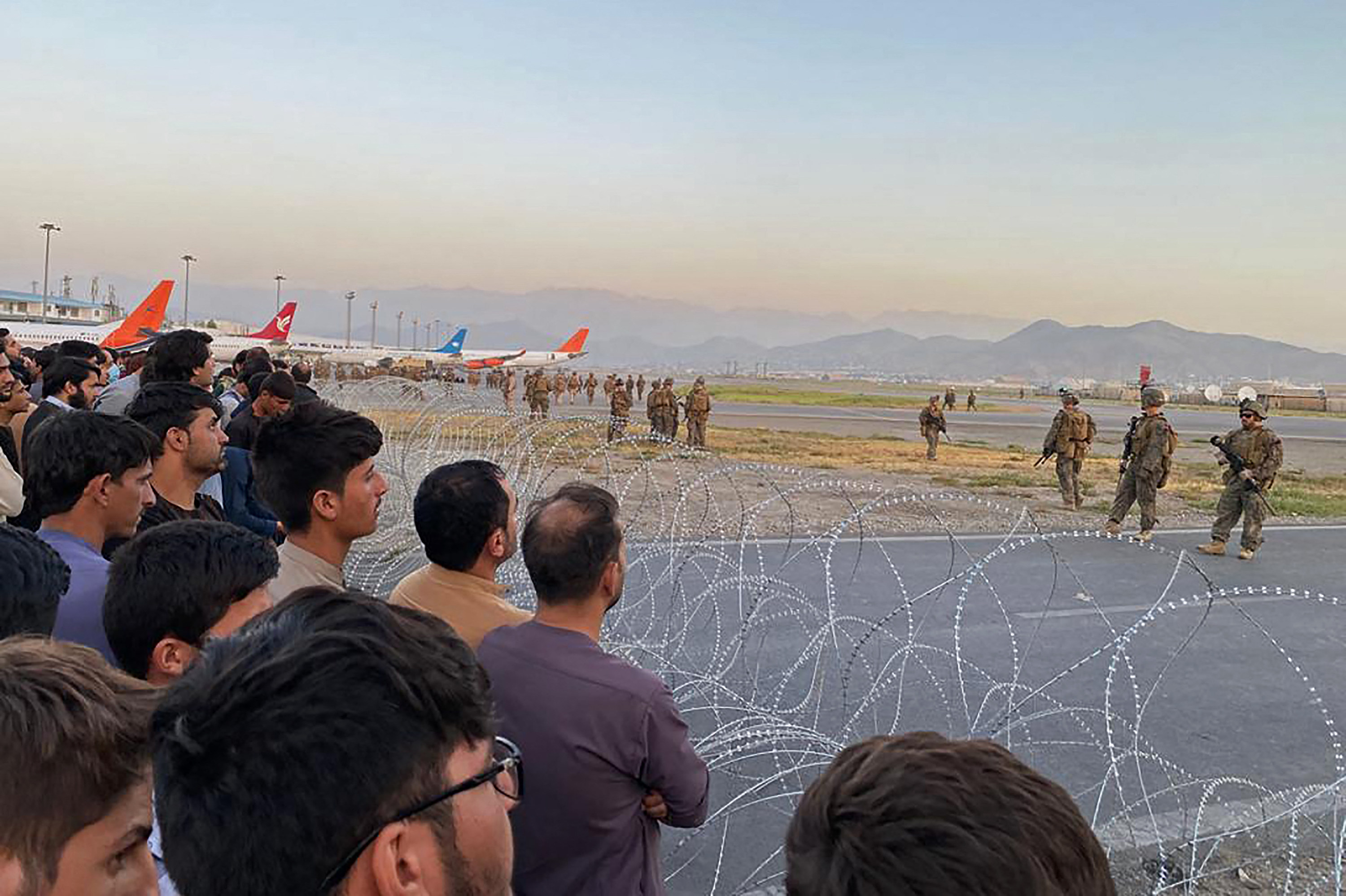 People behind barbed wire look out at planes and soldiers at the airport