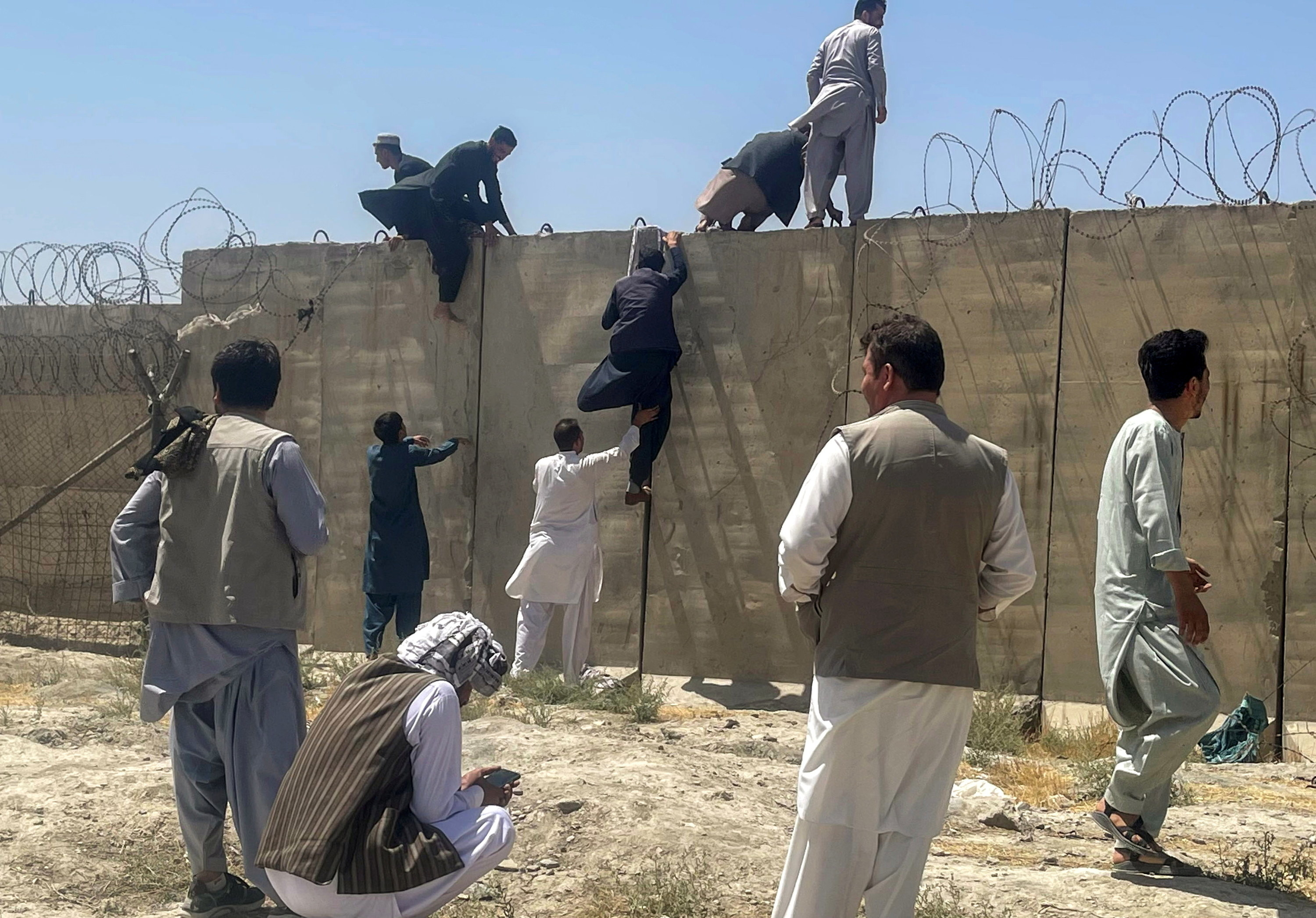 Men are climbing a wall with barbed wire
