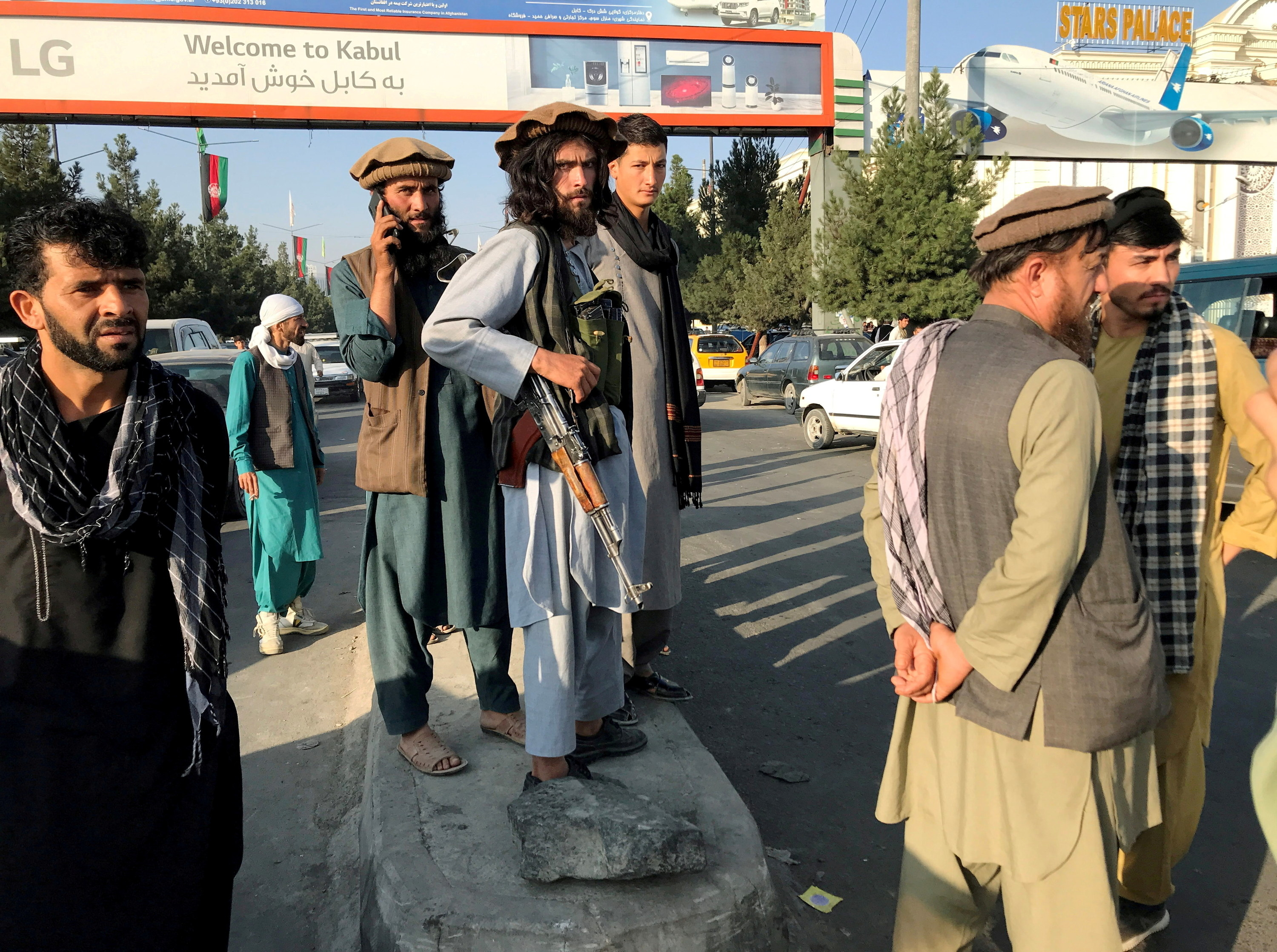 Taliban members with guns stand under a sign saying welcome to Kabul