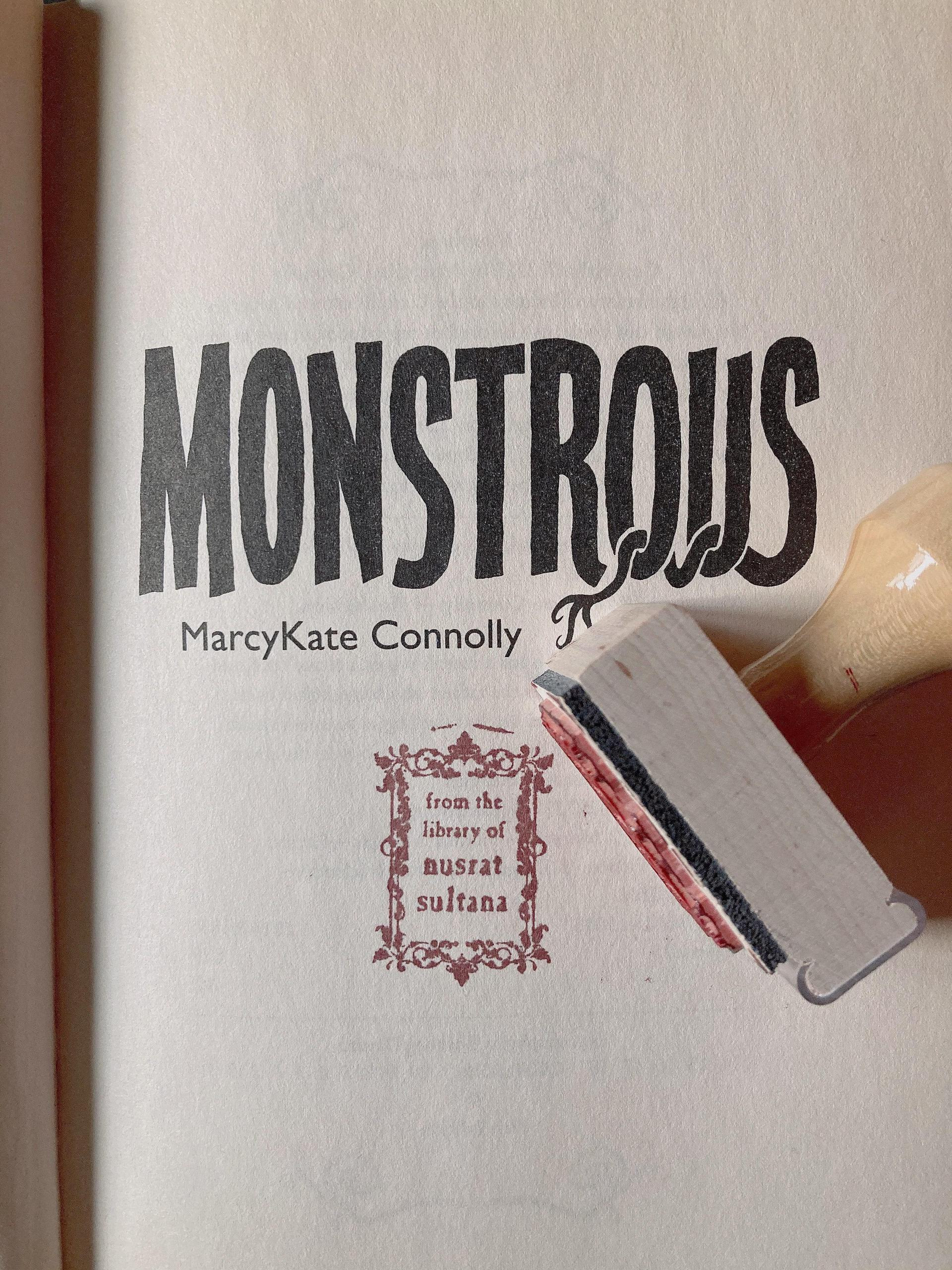 """the title page of the book """"monstrous"""" stamped with """"from the library of nusrat sultana"""" on it in red ink, and the stamp with a handle sitting on the page"""