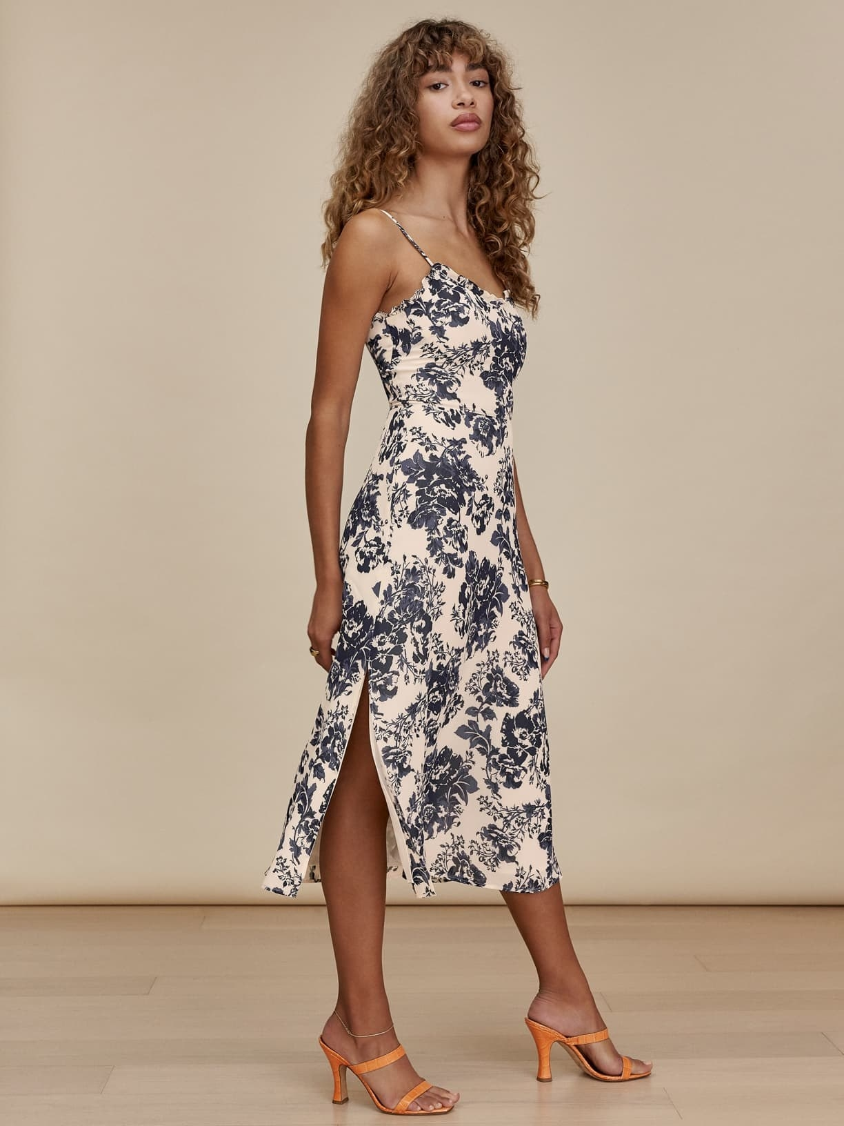 model wearing the mid-length spaghetti strap dress in white with blue flowers all over it