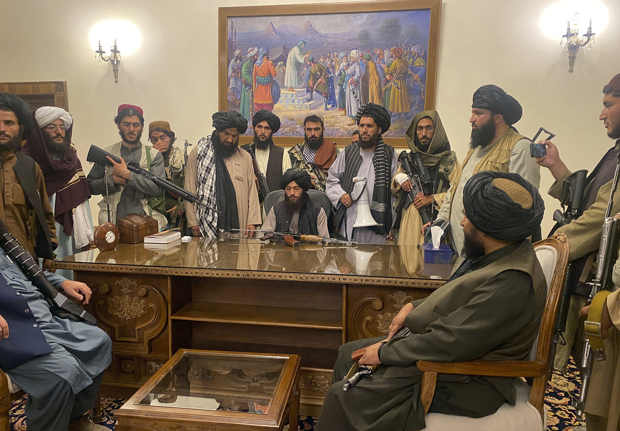 A group shot of Taliban fighters with guns at the presidential desk