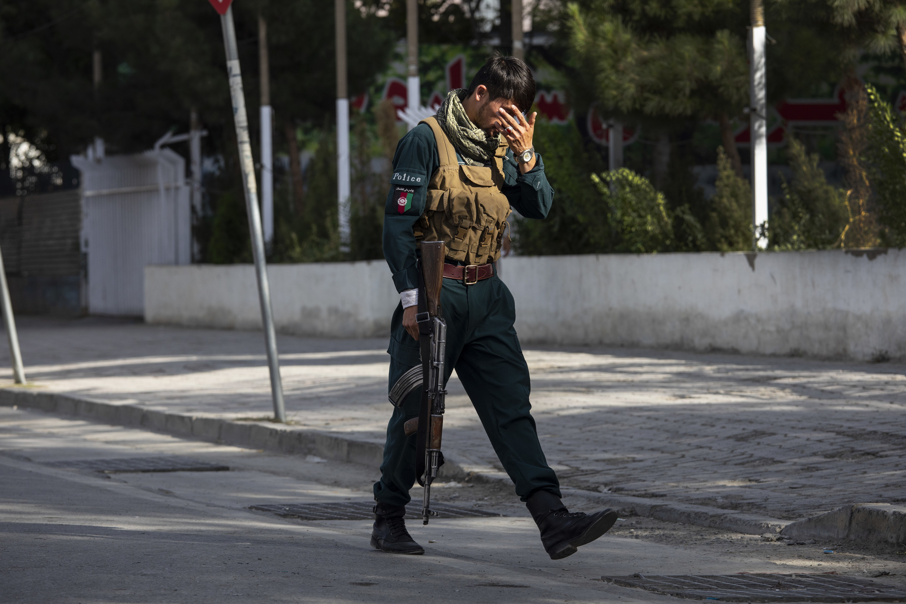 An Afghan police officer with his head in his hands