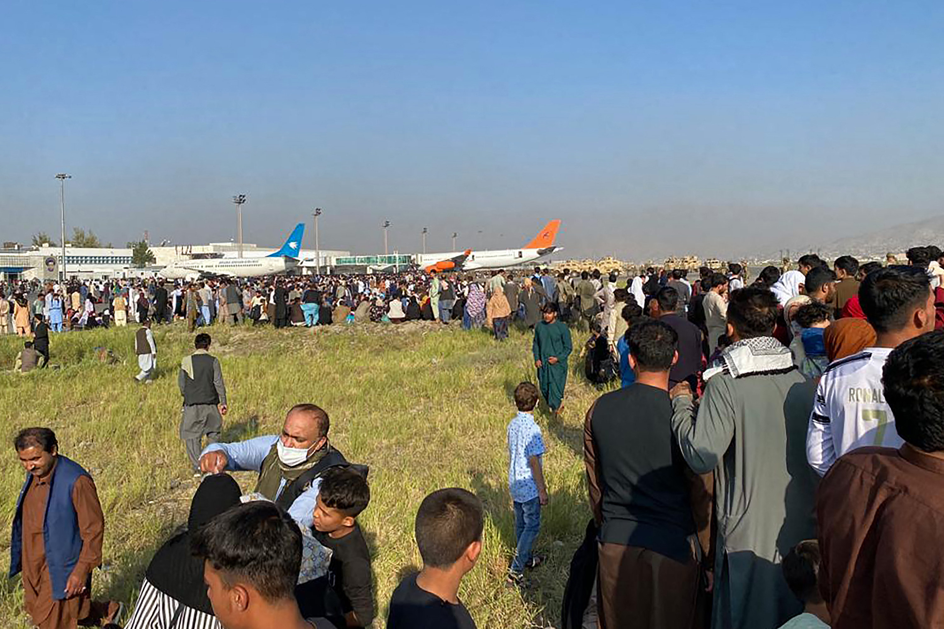 Hundreds crowd the grass and tarmac at the airport