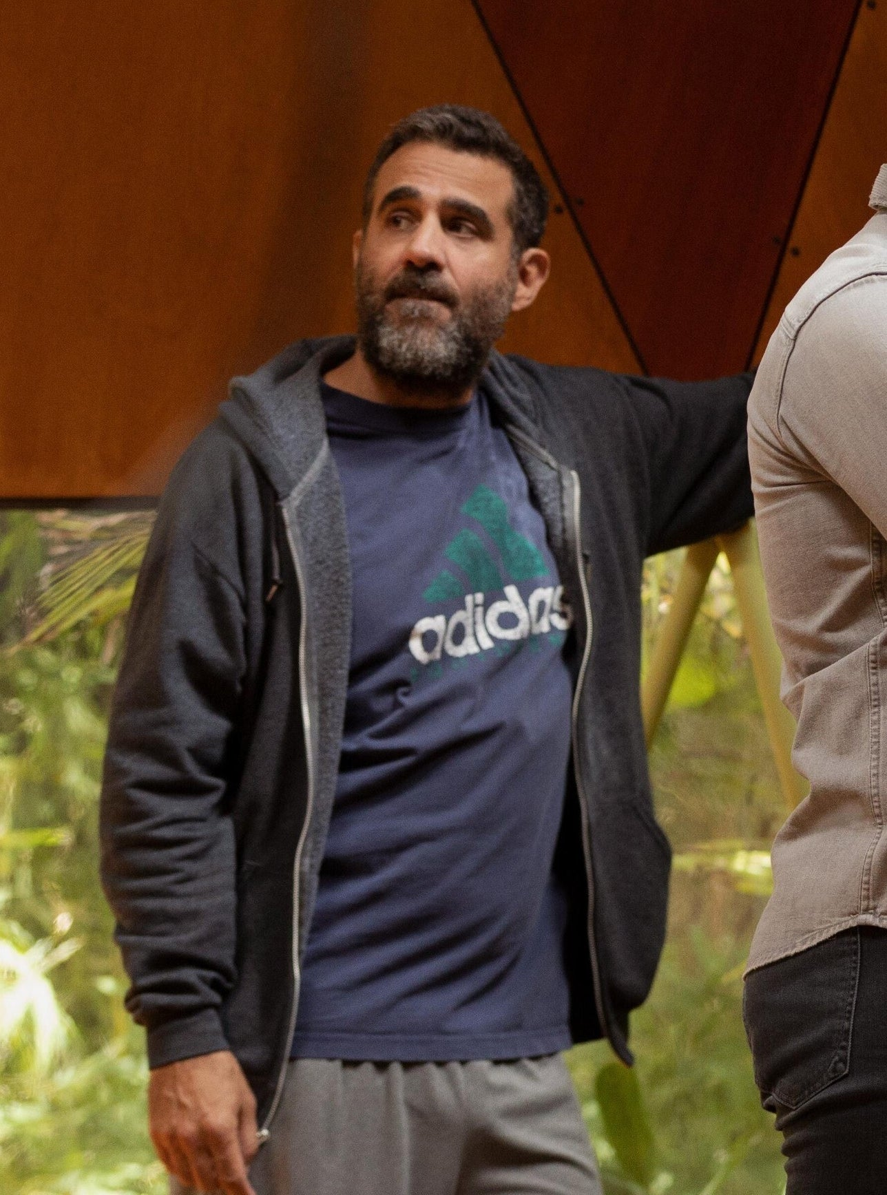 Bobby Cannavale leans against the side of the meeting room