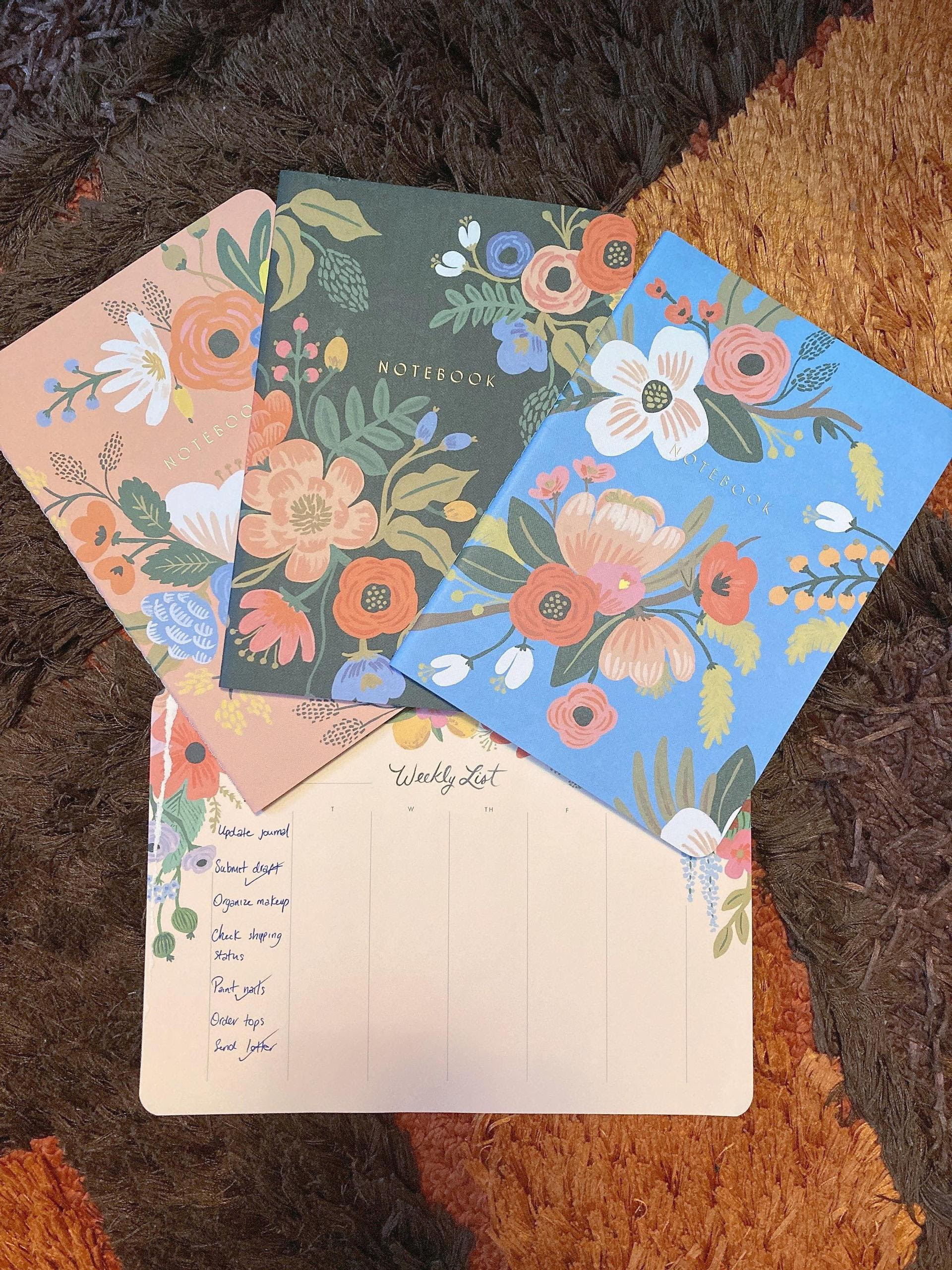 """three illustrated floral notebooks and a desk pad titled """"weekly list"""" with daily columns for planning"""