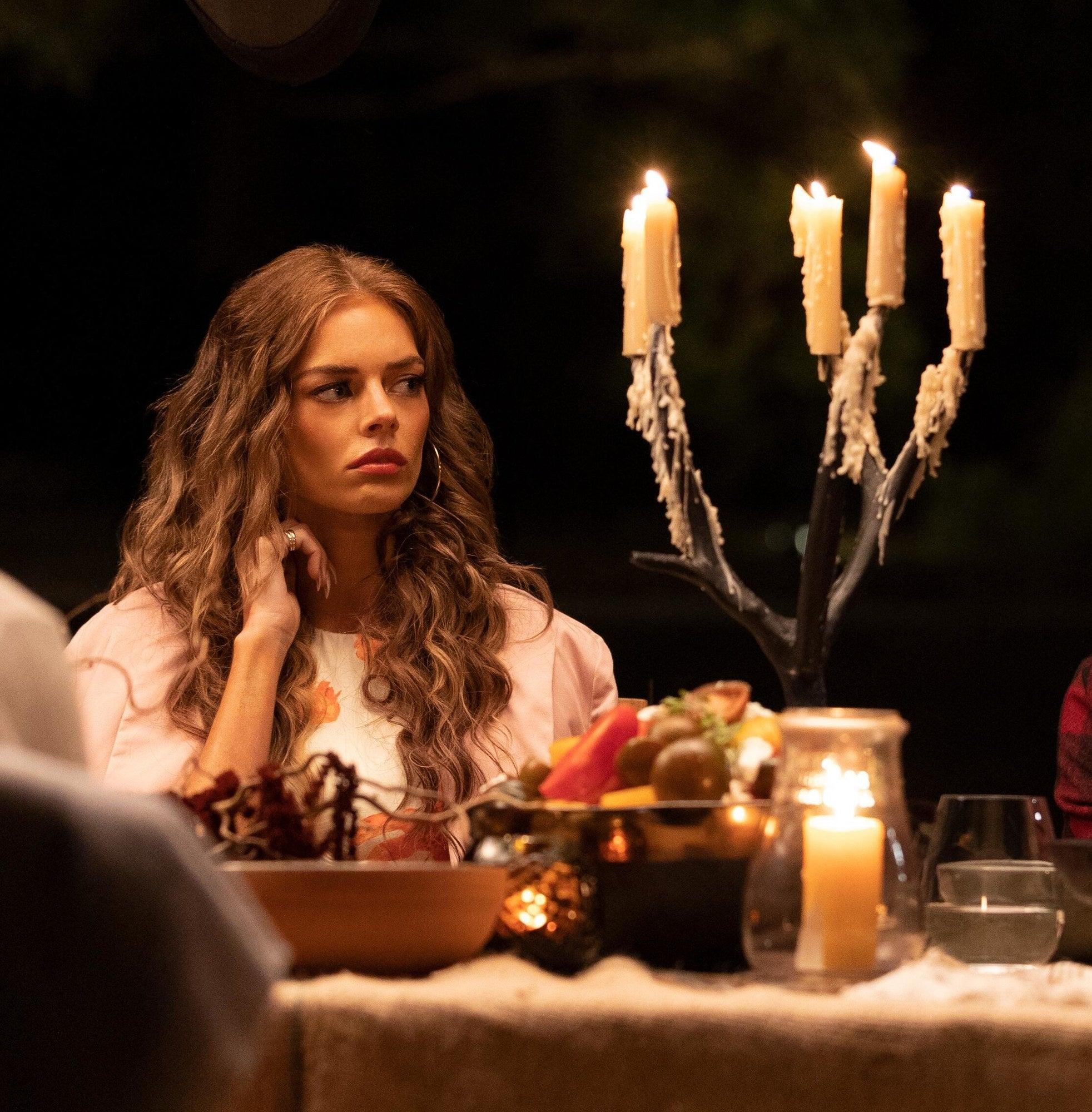 Samara Weaving sits at a dinner table
