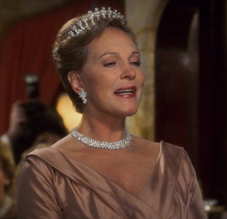 the queen wears a diamond necklace, earrings, and tiara