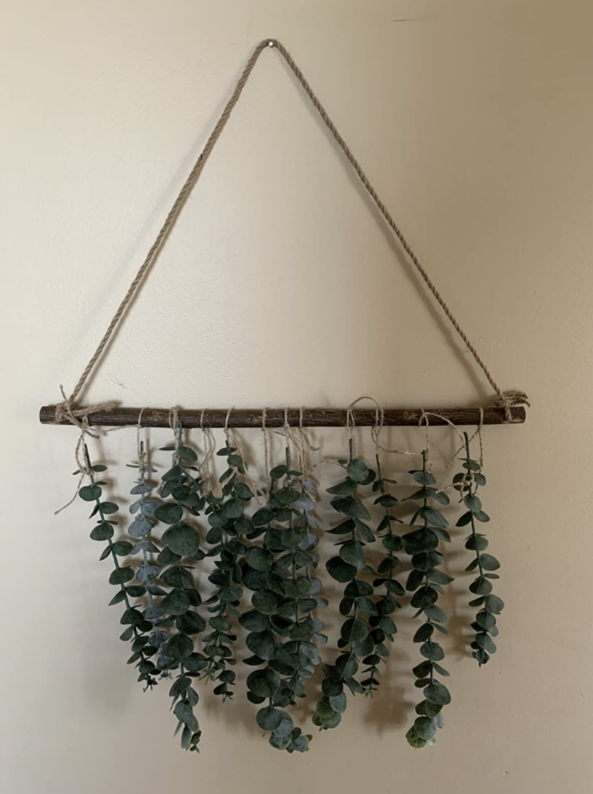 The small wall hanging with a curtain of eucalyptus coming down from a wooden rod