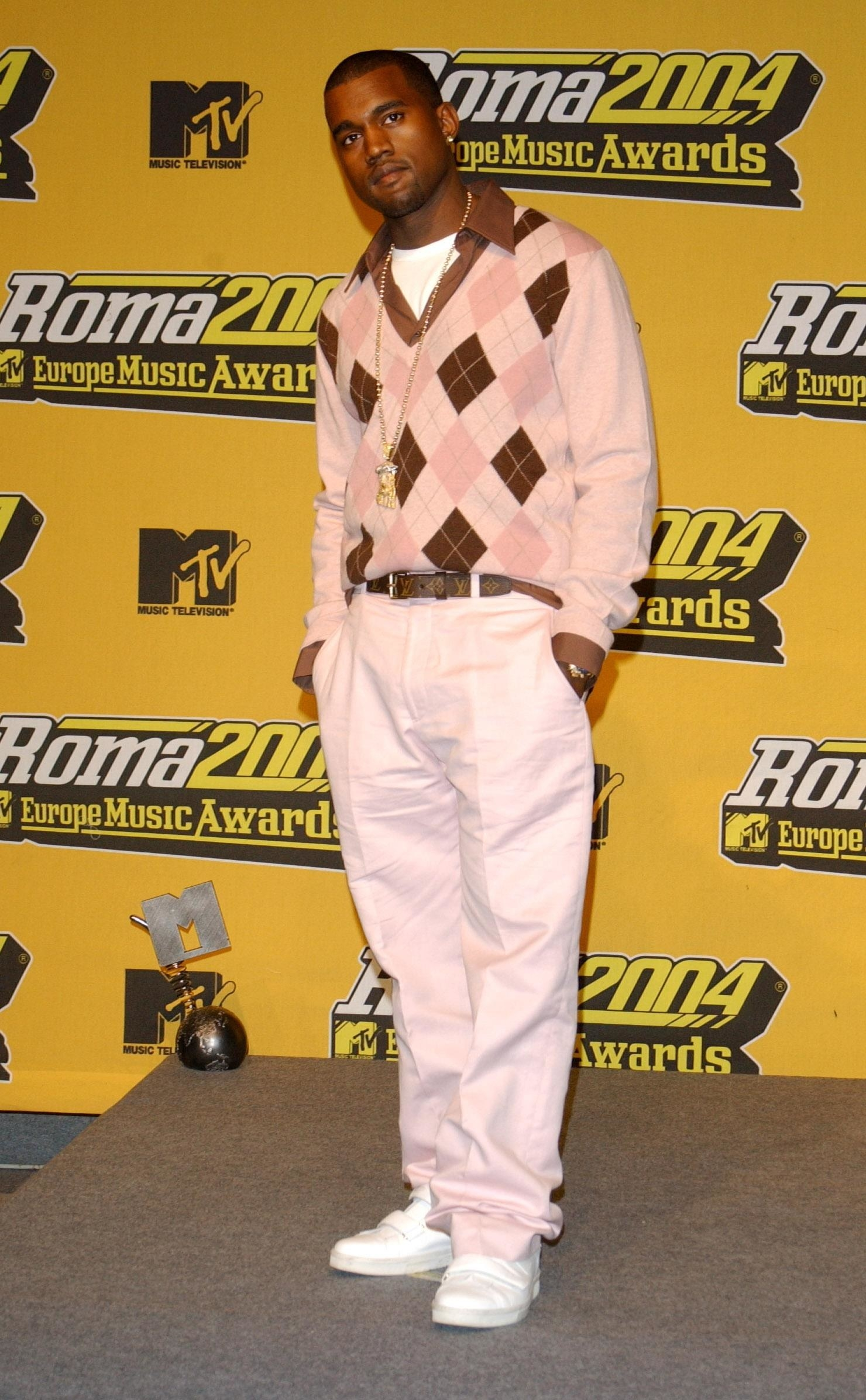 Kanye wears an argyle v-neck sweater with a collared shirt underneath it. He wears baggy dress pants and matching boots.