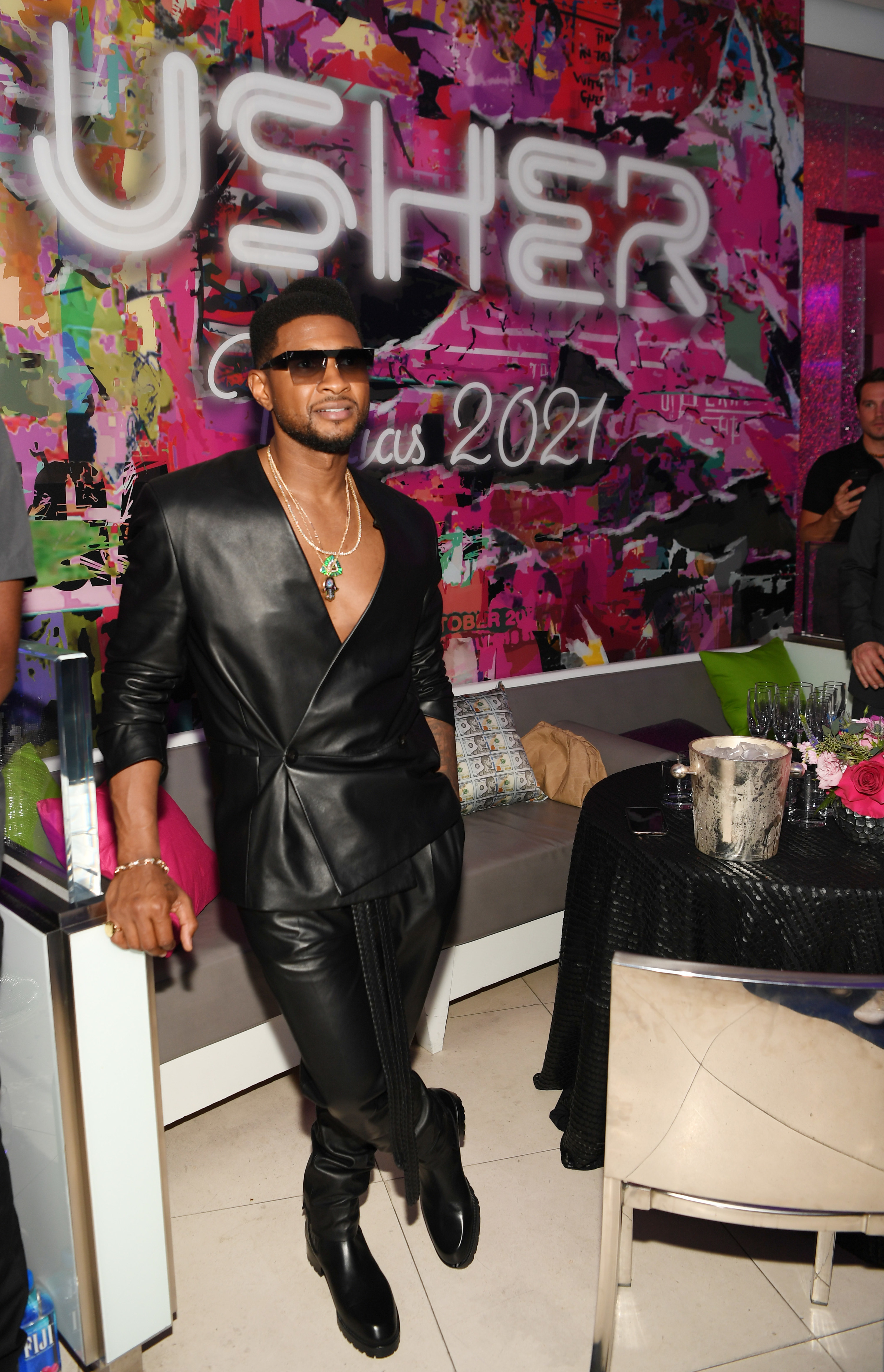Usher wears a leather jacket with no shirt underneath, leather pants, boots, and sunglasses.