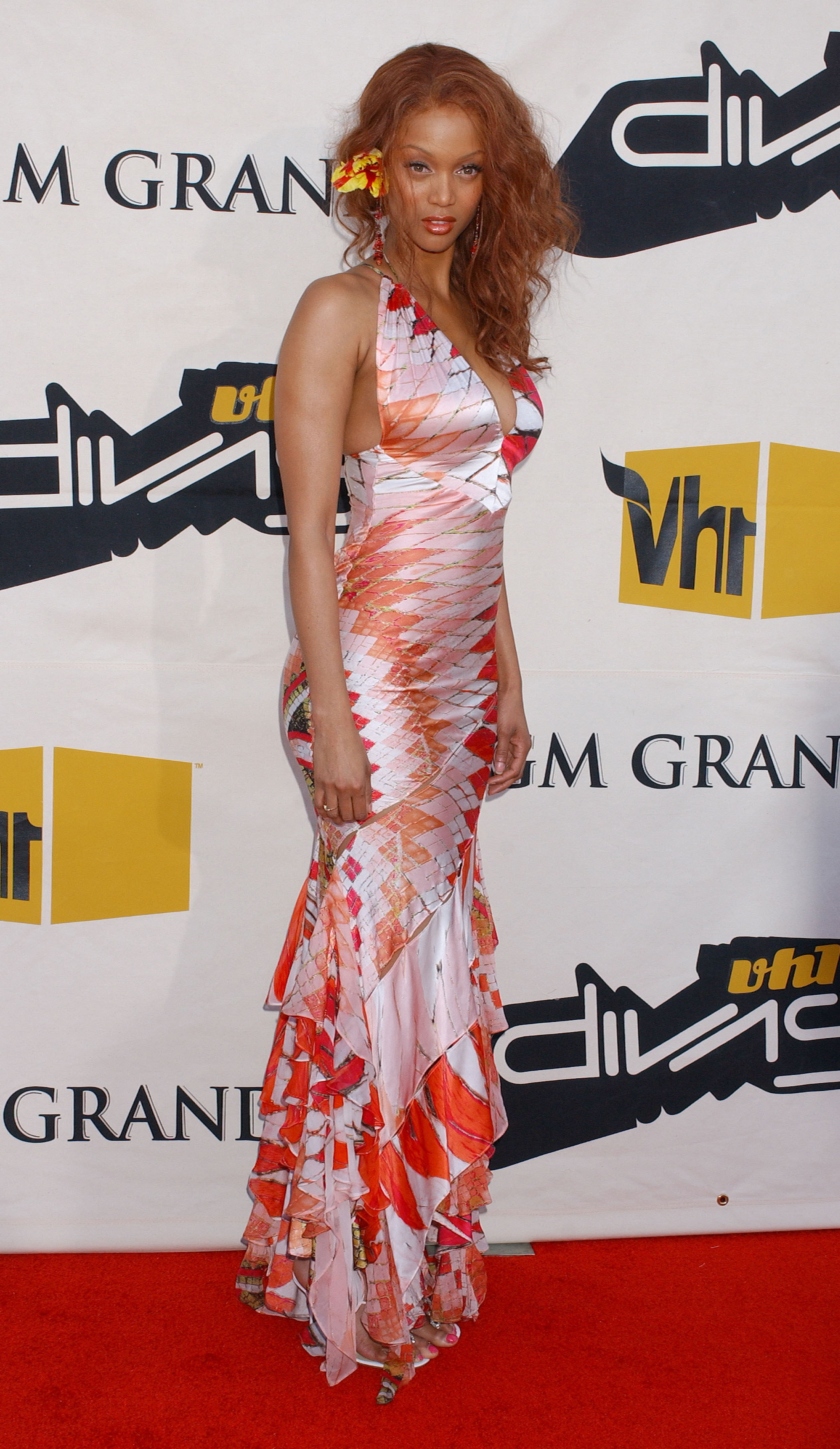 Tyra wears a long patterned halter gown with ruffles at the bottom and a flower in her hair.