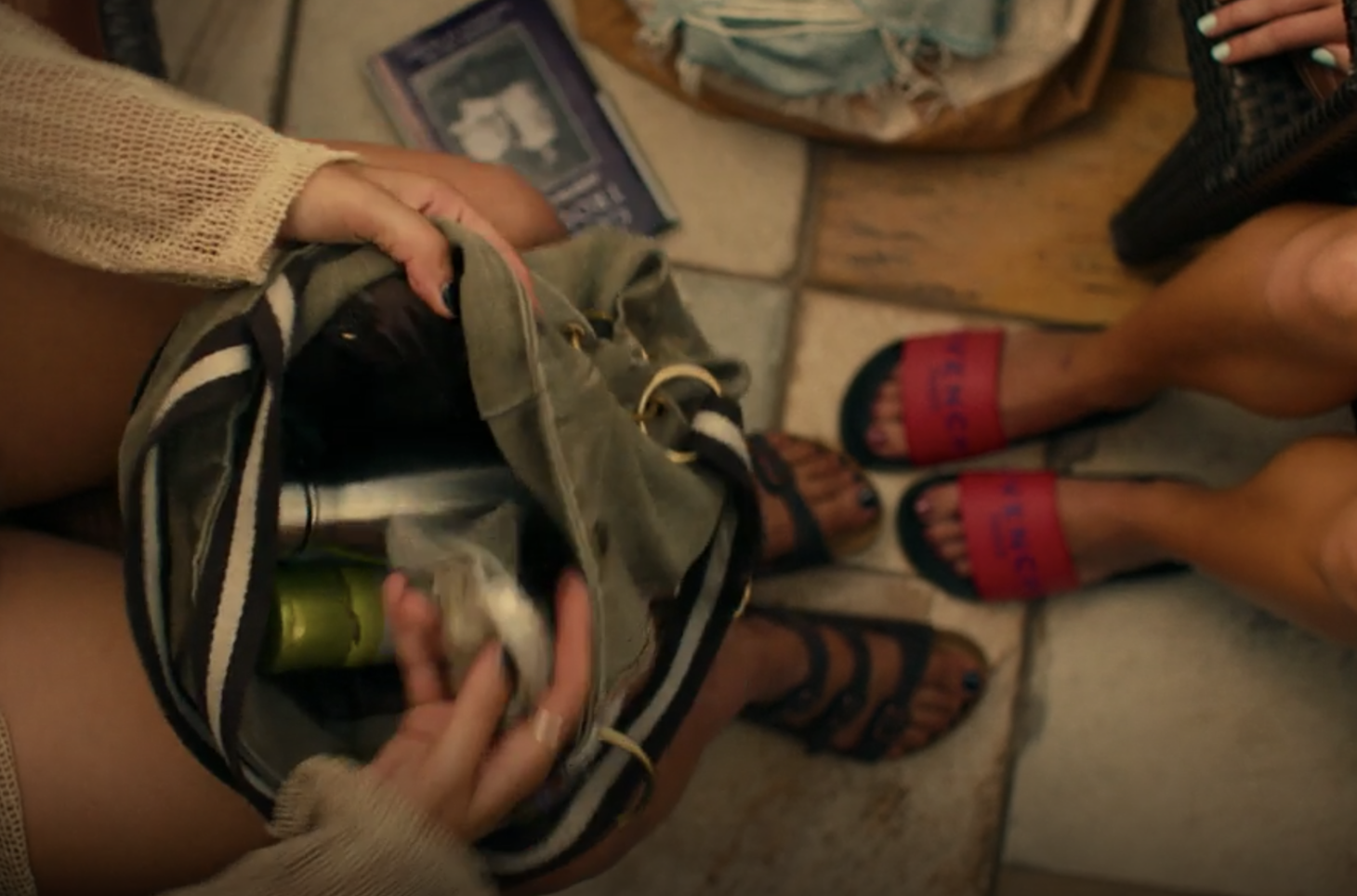 Birds eye view of the floor as Paula digs through her bag setting Gender Trouble to the side