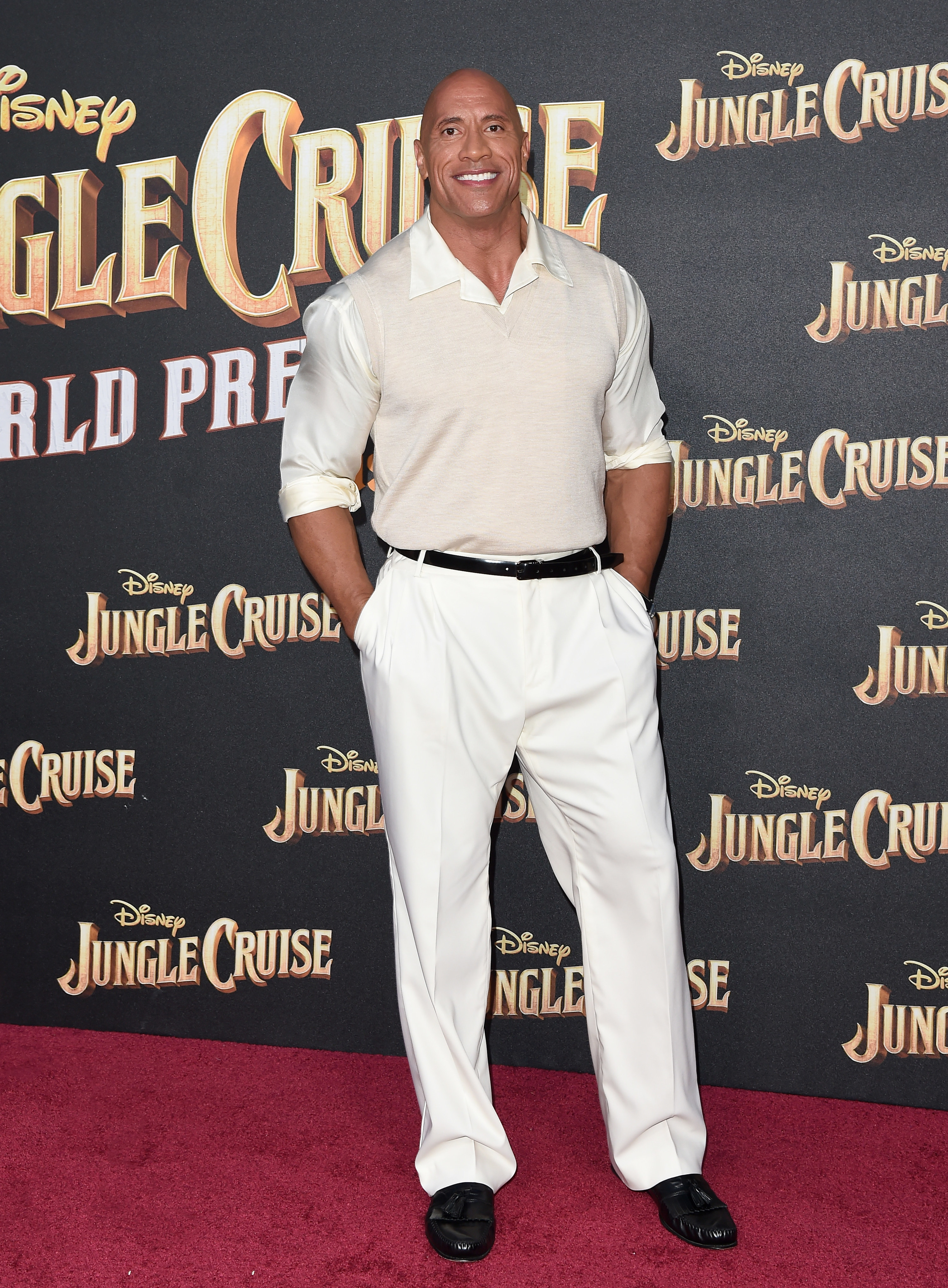 Dwayne wears a monochromatic outfit with a sweater vest, button-down shirt, and dress pants.