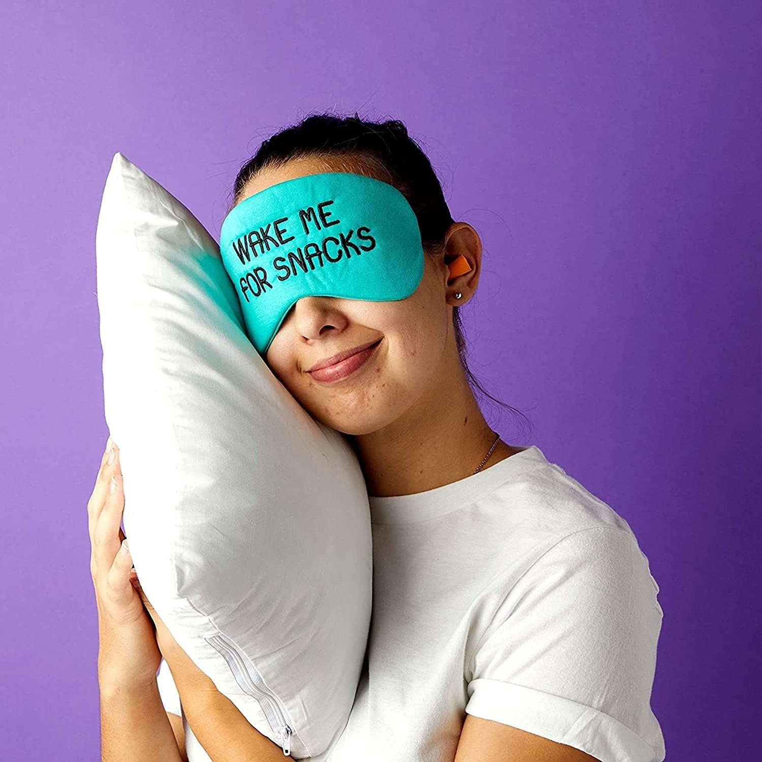 """A person wearing the eye mask that reads, """"Wake me for snacks"""""""