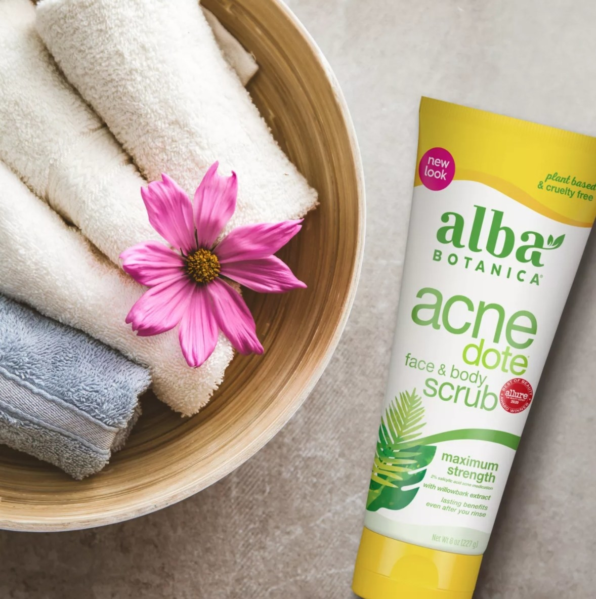 Tube of Alba botanica scrub next to towels