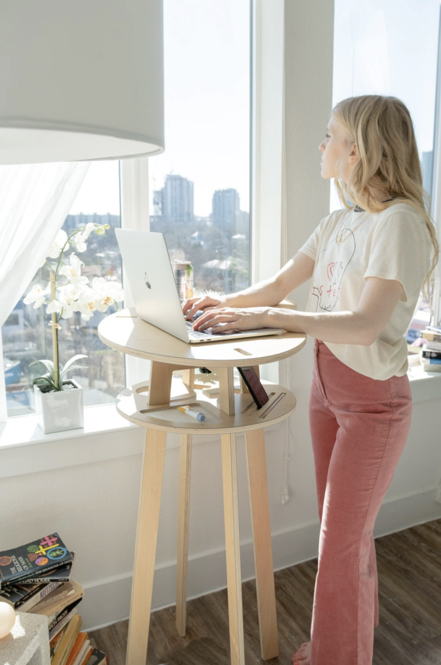 model standing at the small standing desk